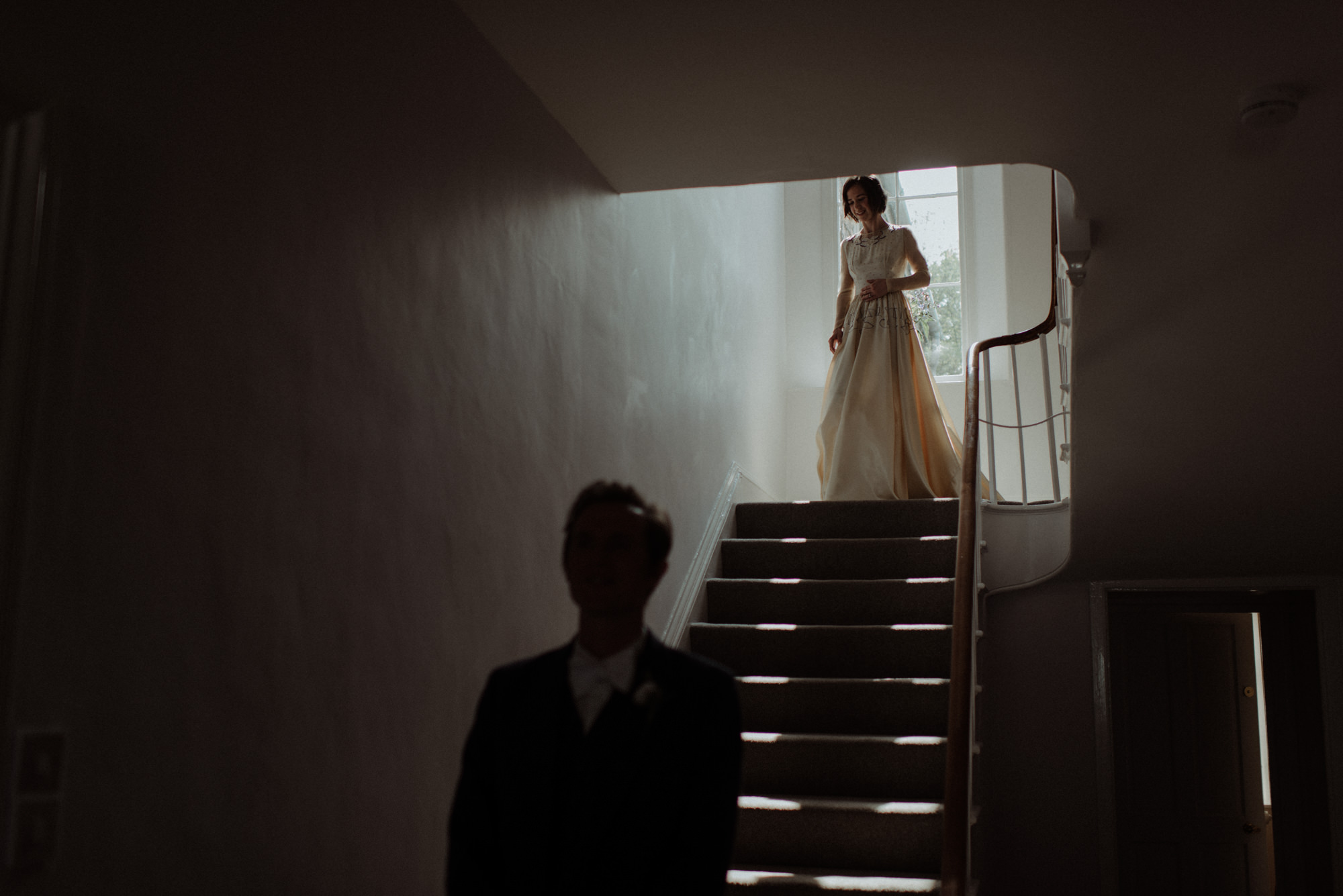 Bride descends stairs to waiting groom in shadow - photo by the Kitcheners - Scotland