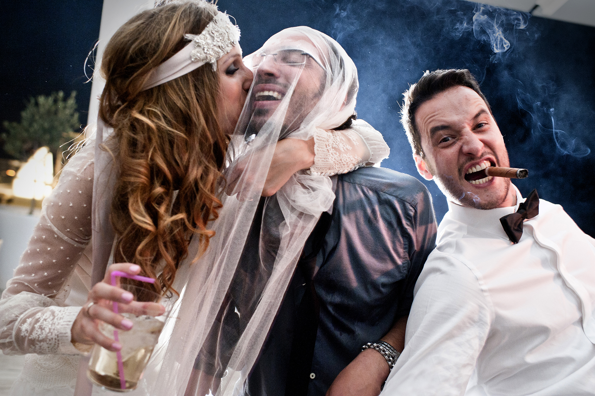 Bride kissing groom wrapped in veil - photo by Victor Lax