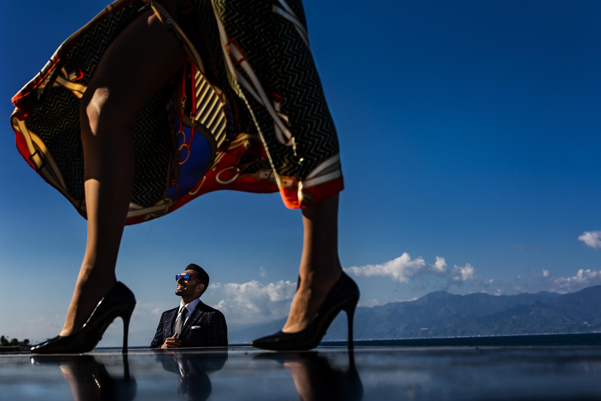 Groom framed between bride's legs - photo by Victor Lax
