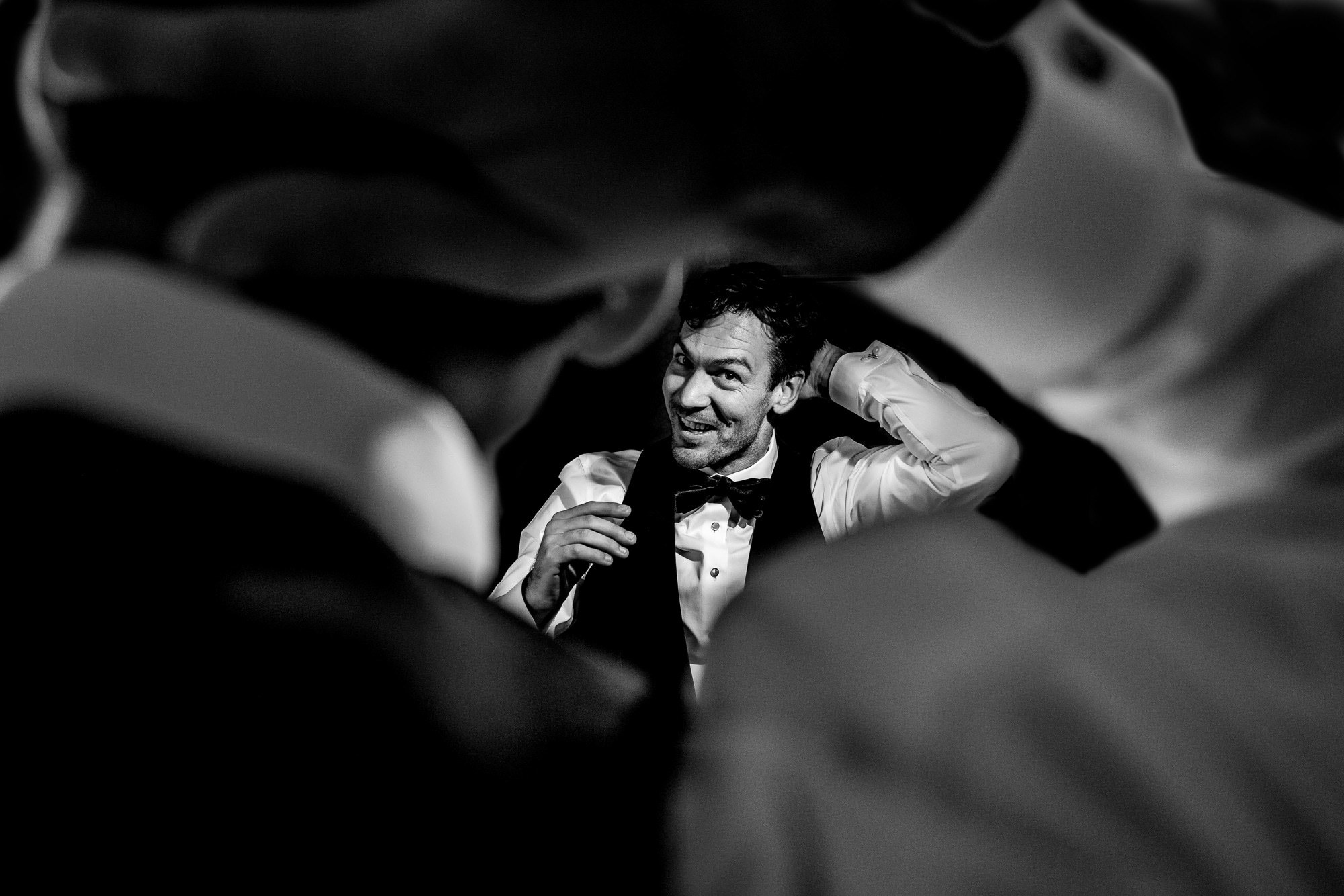 Happy groom checks himself out in the mirror - photo by Jos Studios - Portland