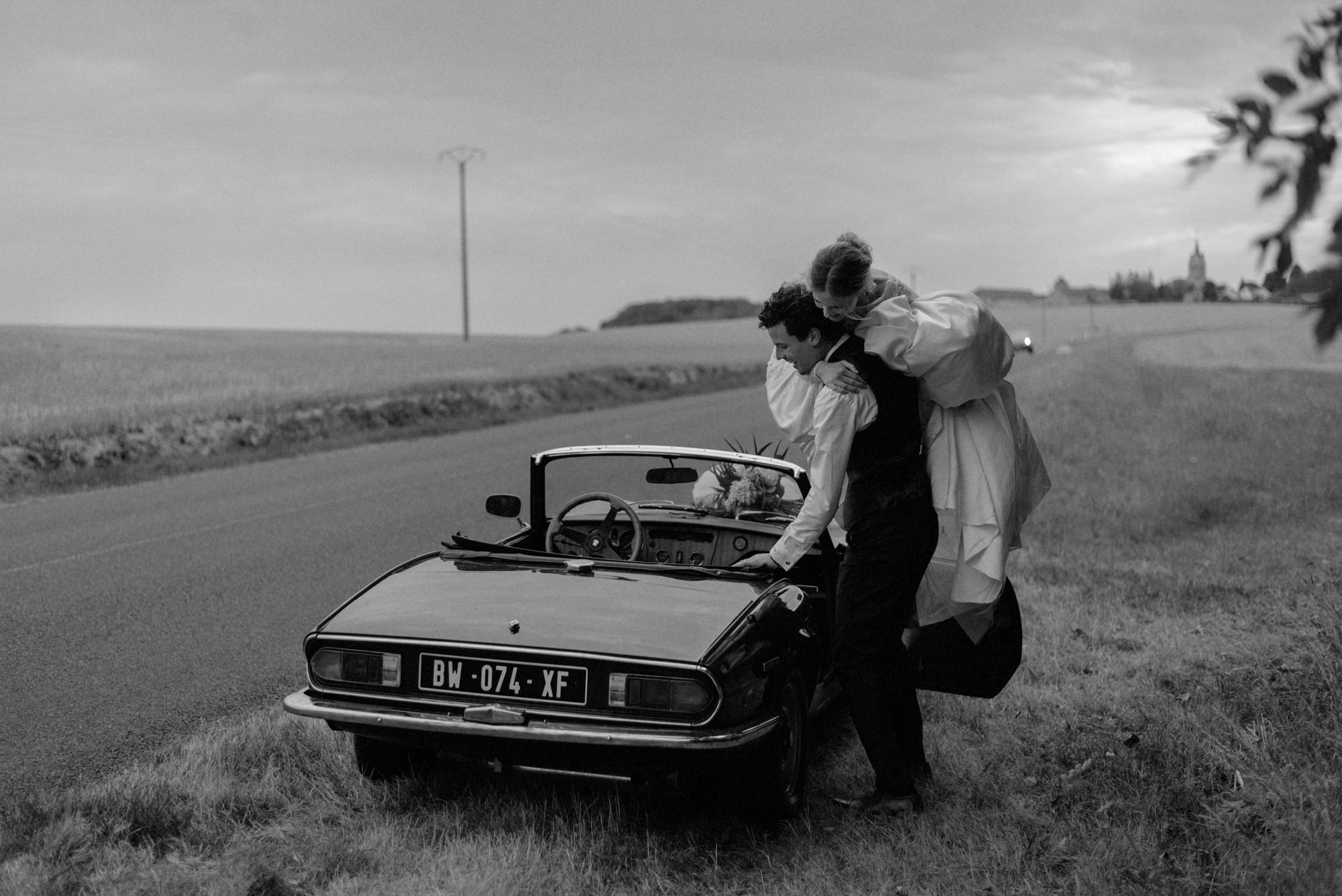 Sweet photo of groom putting bride into convertible by The Kitcheners