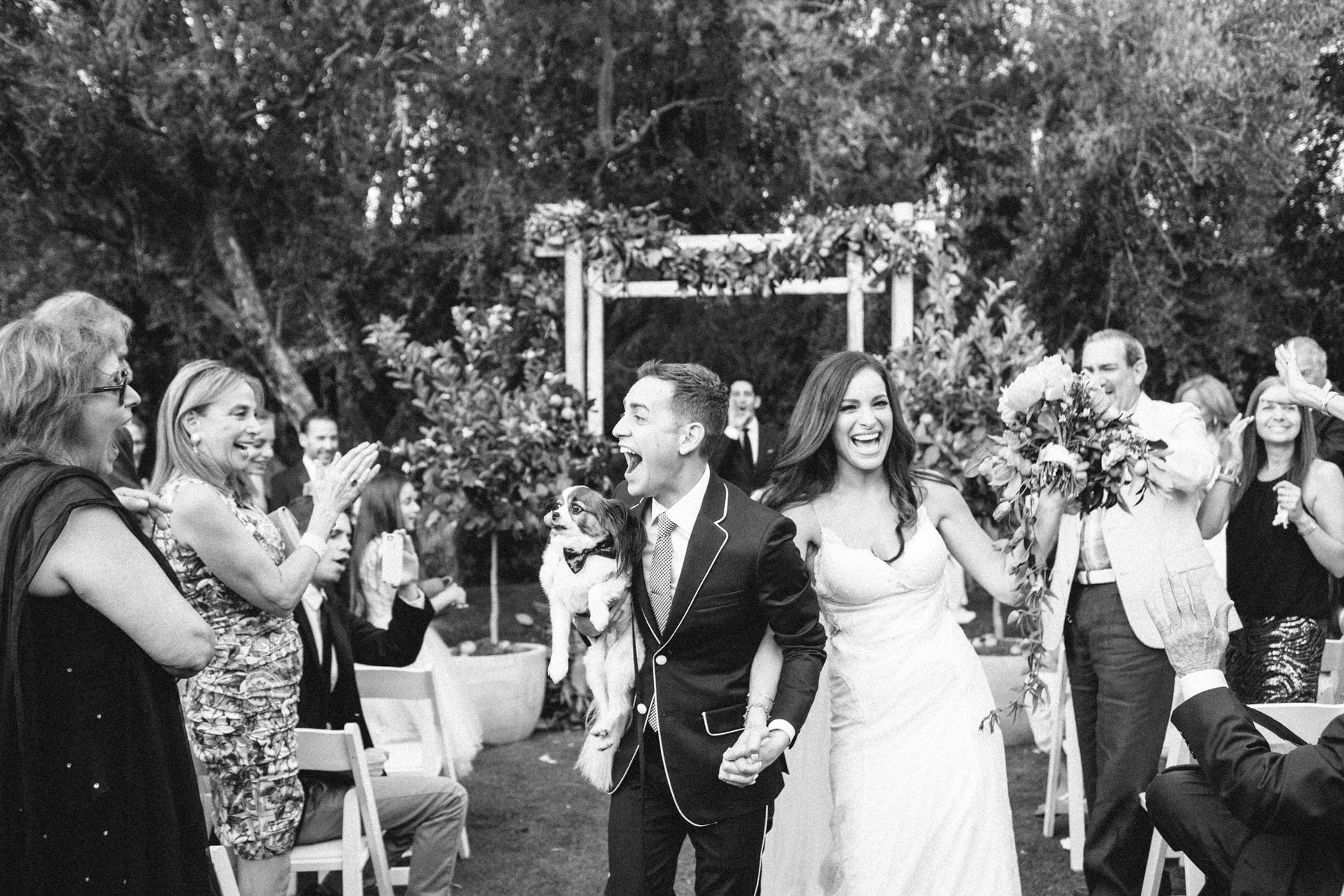 Happy couple leaves ceremony with puppy - photo by Corbin Gurkin