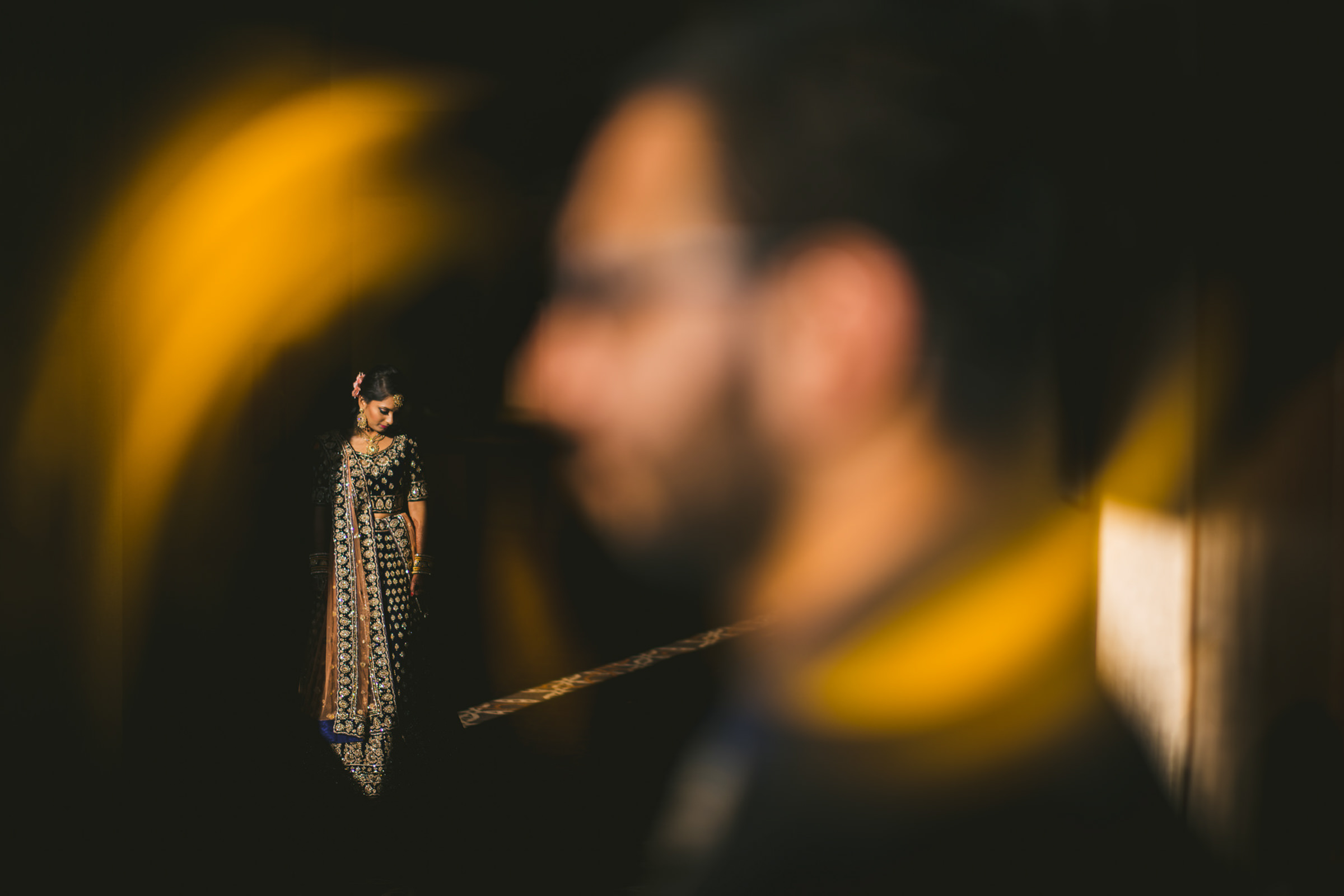 -Indian bride in black and gold lehenga with groom in foreground - photo by Sam Hurd - DC