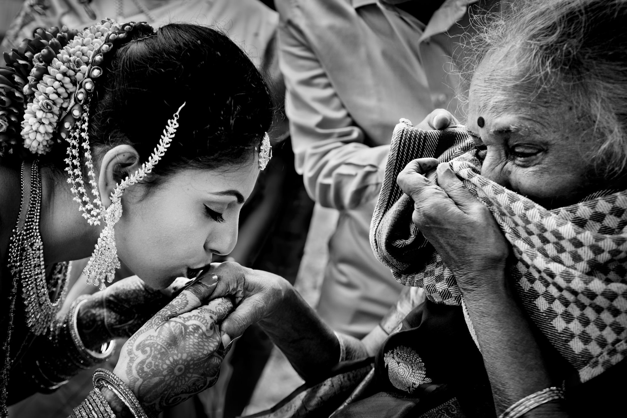 Indian bride kisses grandmother's hand during ceremony - photo by Two Mann Studios