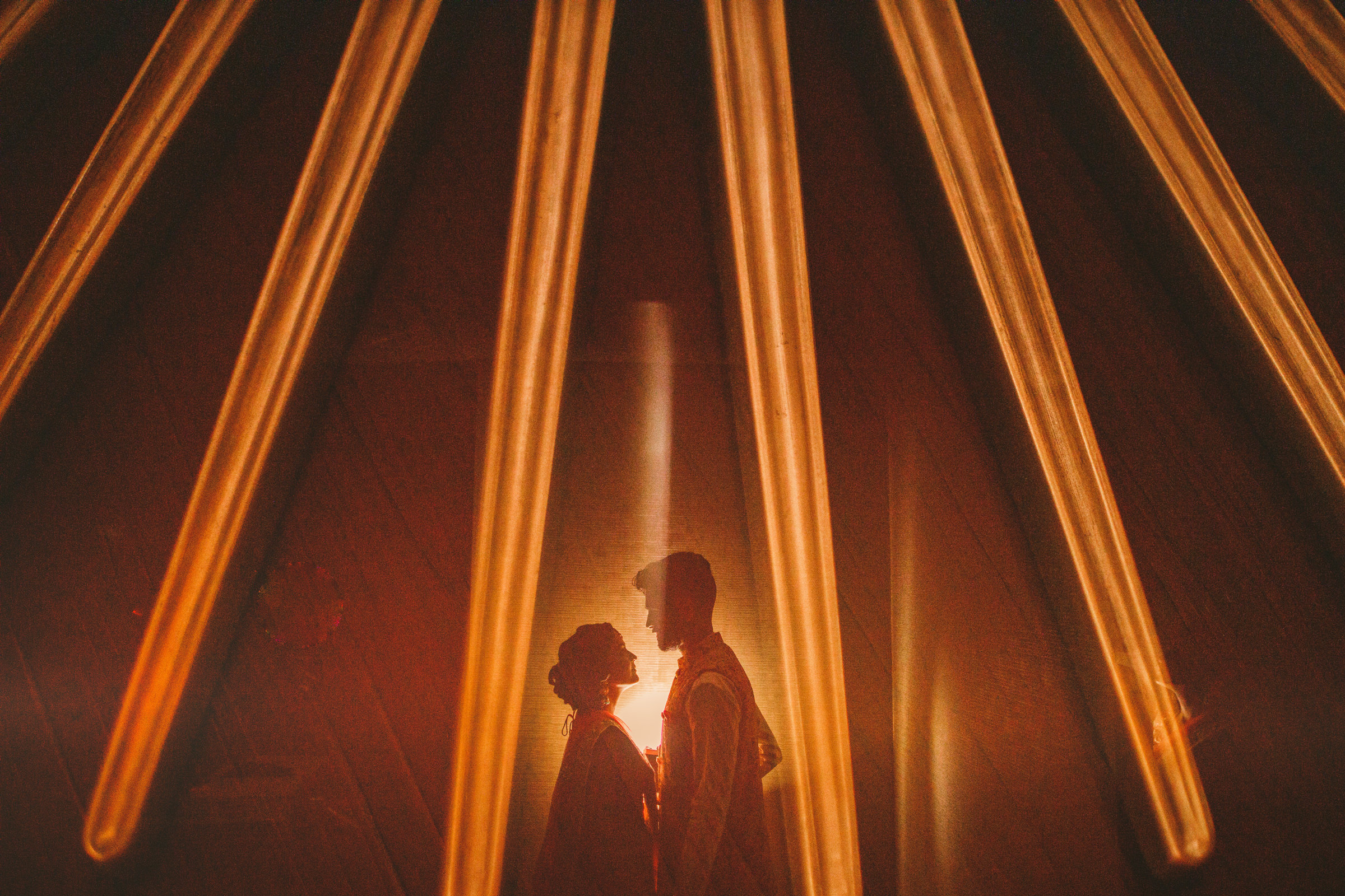 Couple of photo reflected on gold sun sculpture - photo by Sam Hurd - DC