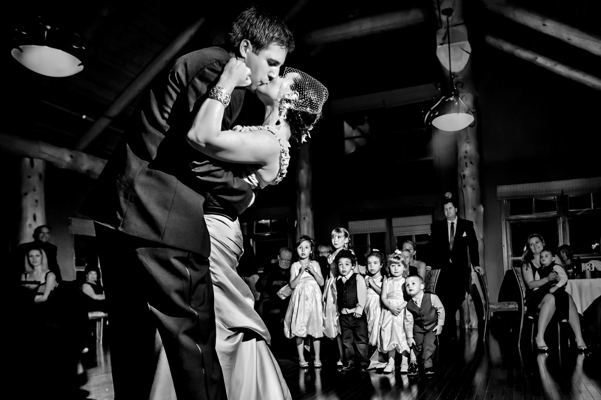 Kids look on while couple kisses on dance floor - photo by Two Mann Studios
