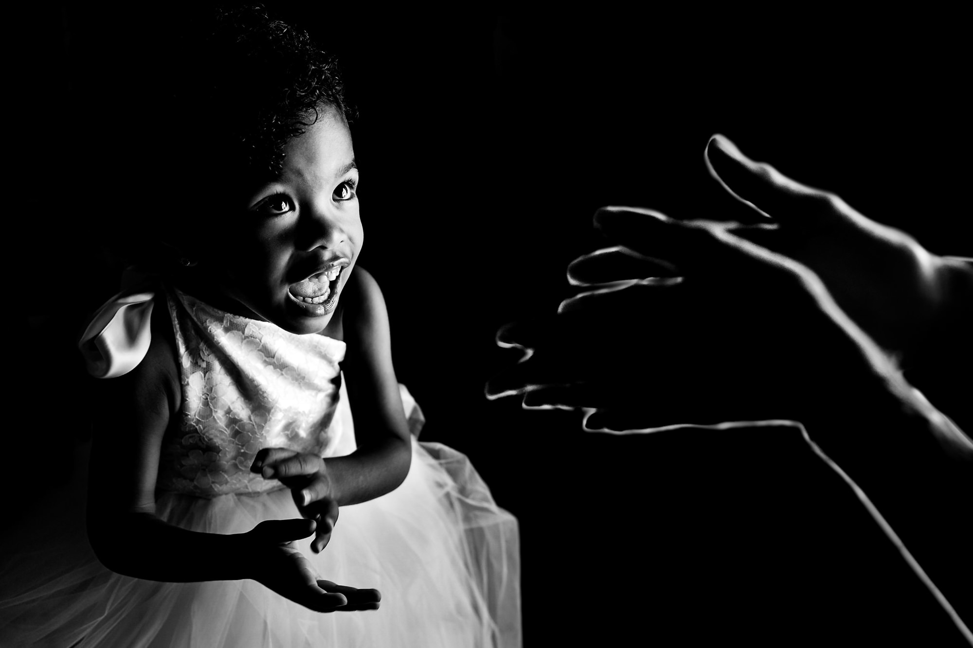Little girl smiles and woman reaches out hands to her - photo by Two Mann Studios