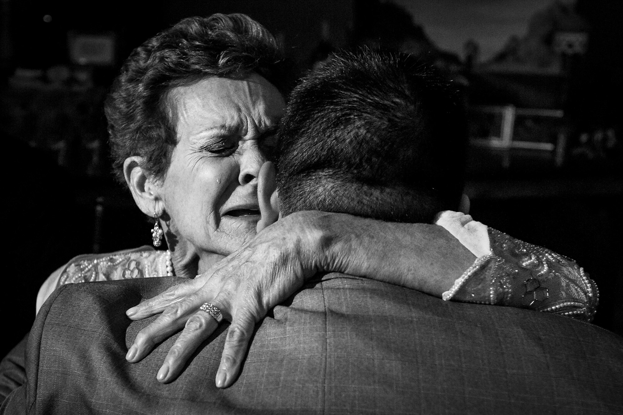 Crying mother embraces her son - photo by Two Mann Studios