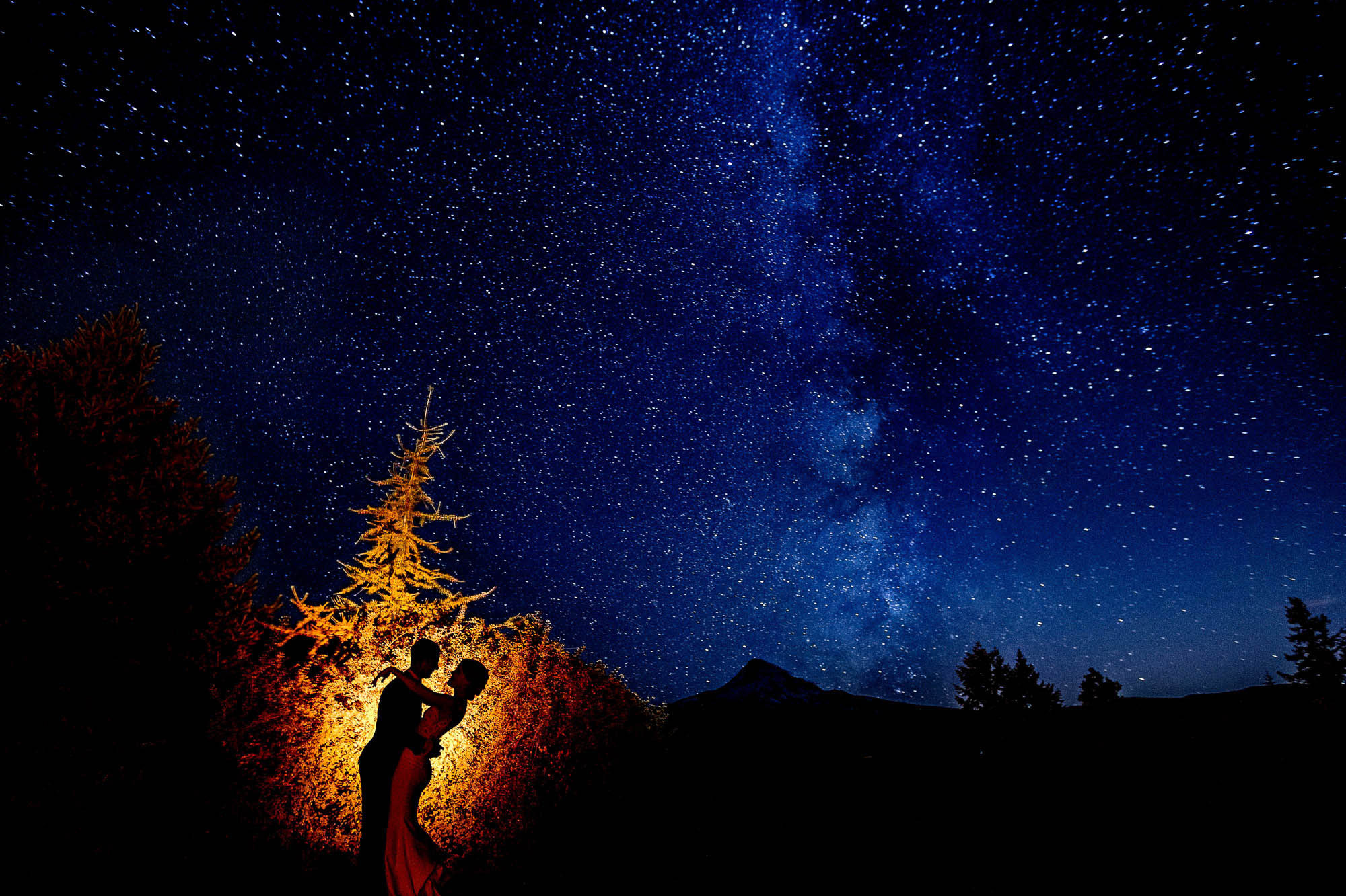 Silhouette of couple against stars by JOS Studios