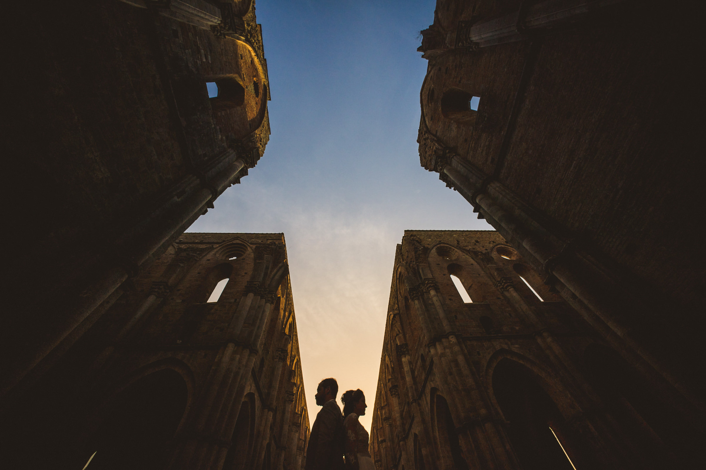 Couple silhouette between stone buildings - photo by Sam Hurd - DC