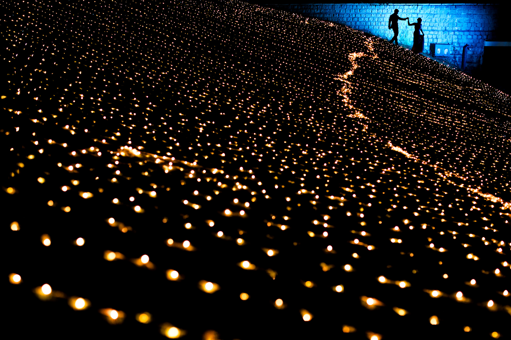 Silhouette of couple walking across field of lights - photo by Two Mann Studios