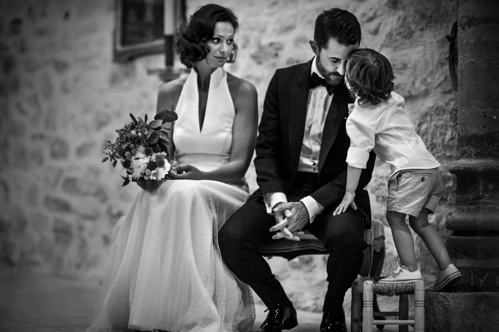 Young son kissing groom during ceremony - photo by Victor Lax