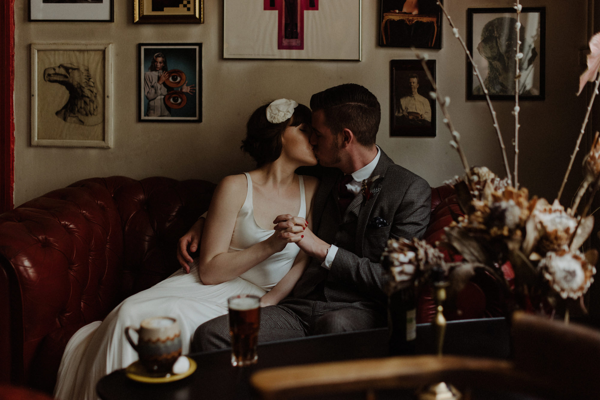 Bride in retro dress kissing groom on couch by The Kitcheners