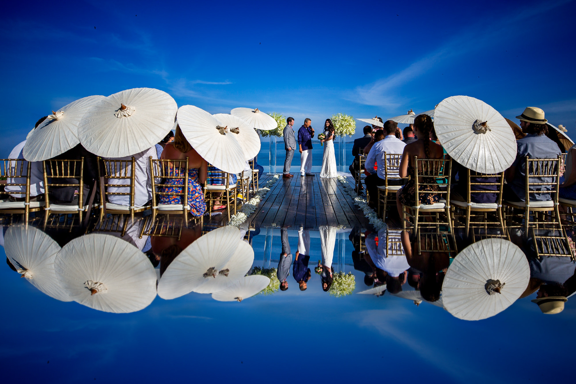 Waterfront ceremony with reflection and guests with white umbrellas - photo by Two Mann Studios