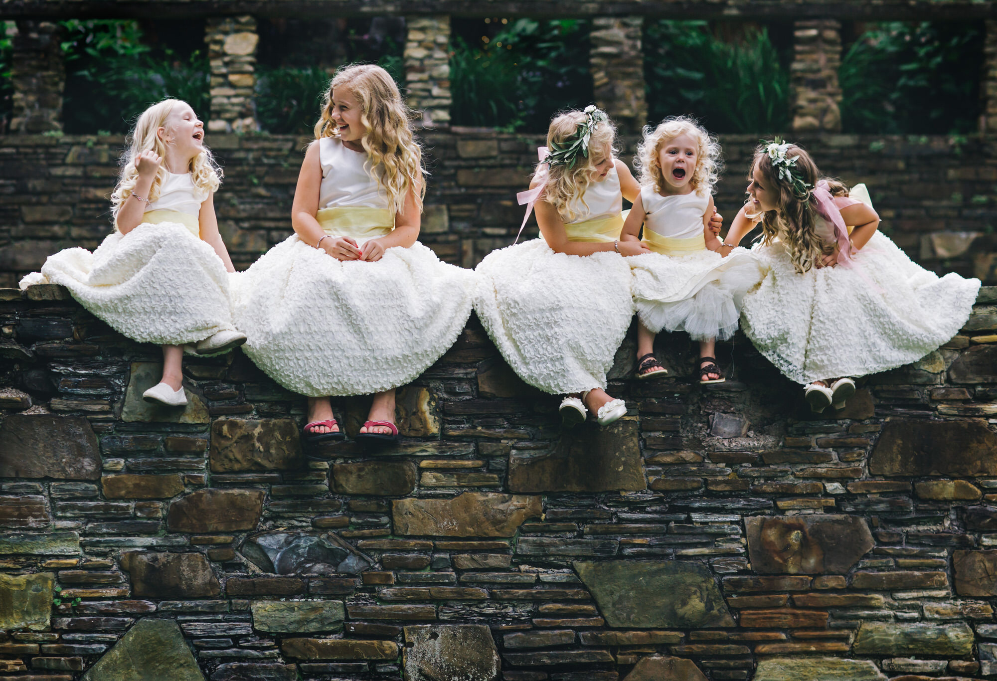 Adorable flower girls setting in a row - photo by Ken Pak