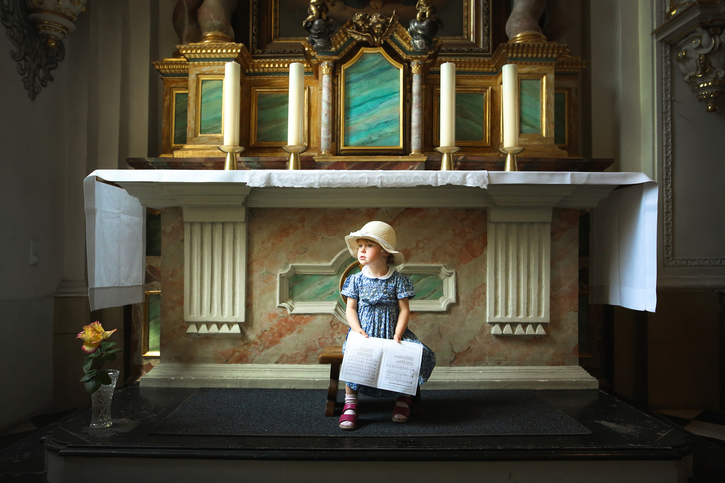 Adorable child with book sitting at altar by Franck Boutonnet