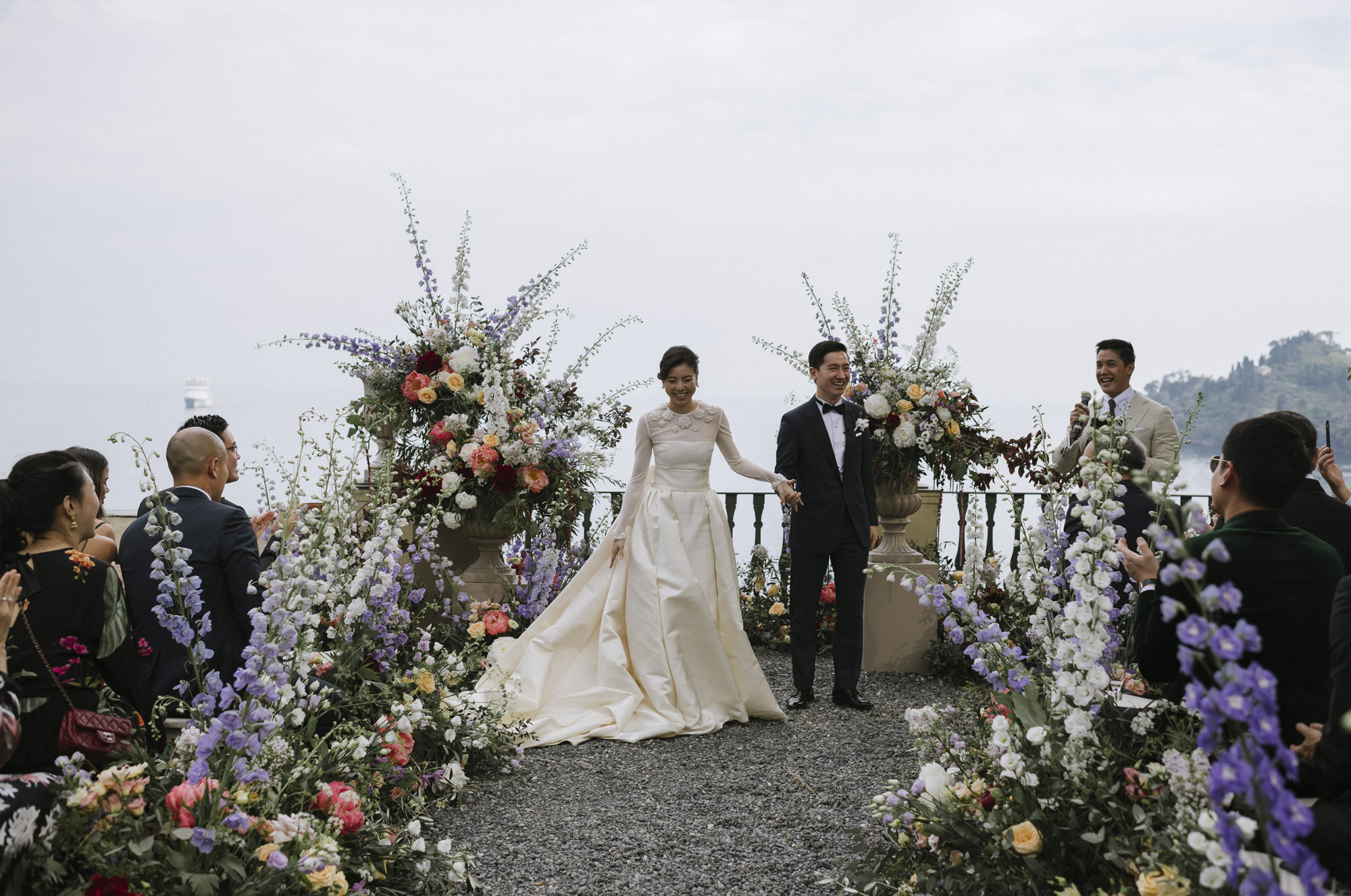 Asian couple just married at beautiful floral arbor, photo by Thierry Joubert