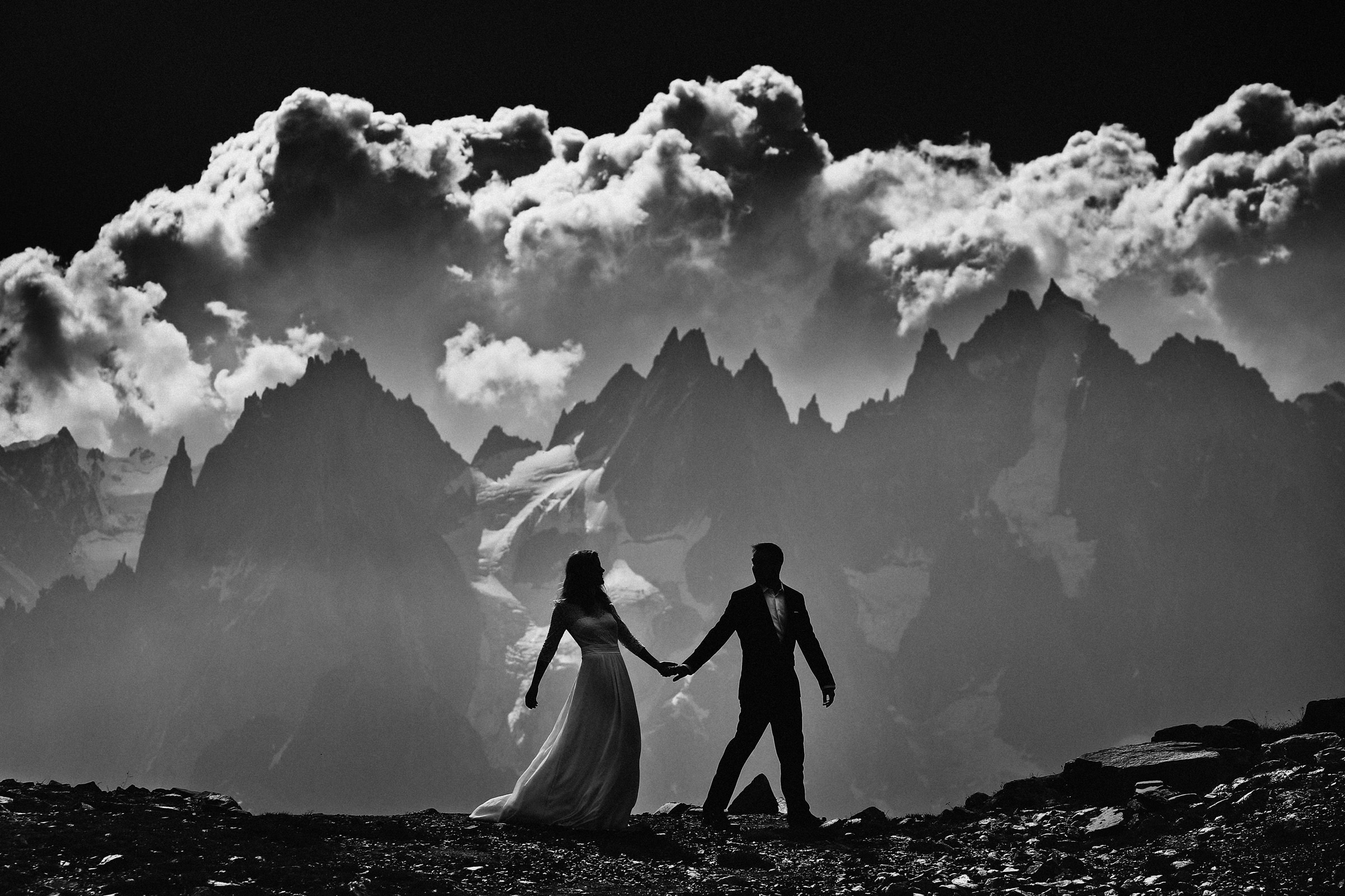 Bride and groom partial silhouette against mountains, by Franck Boutonnet