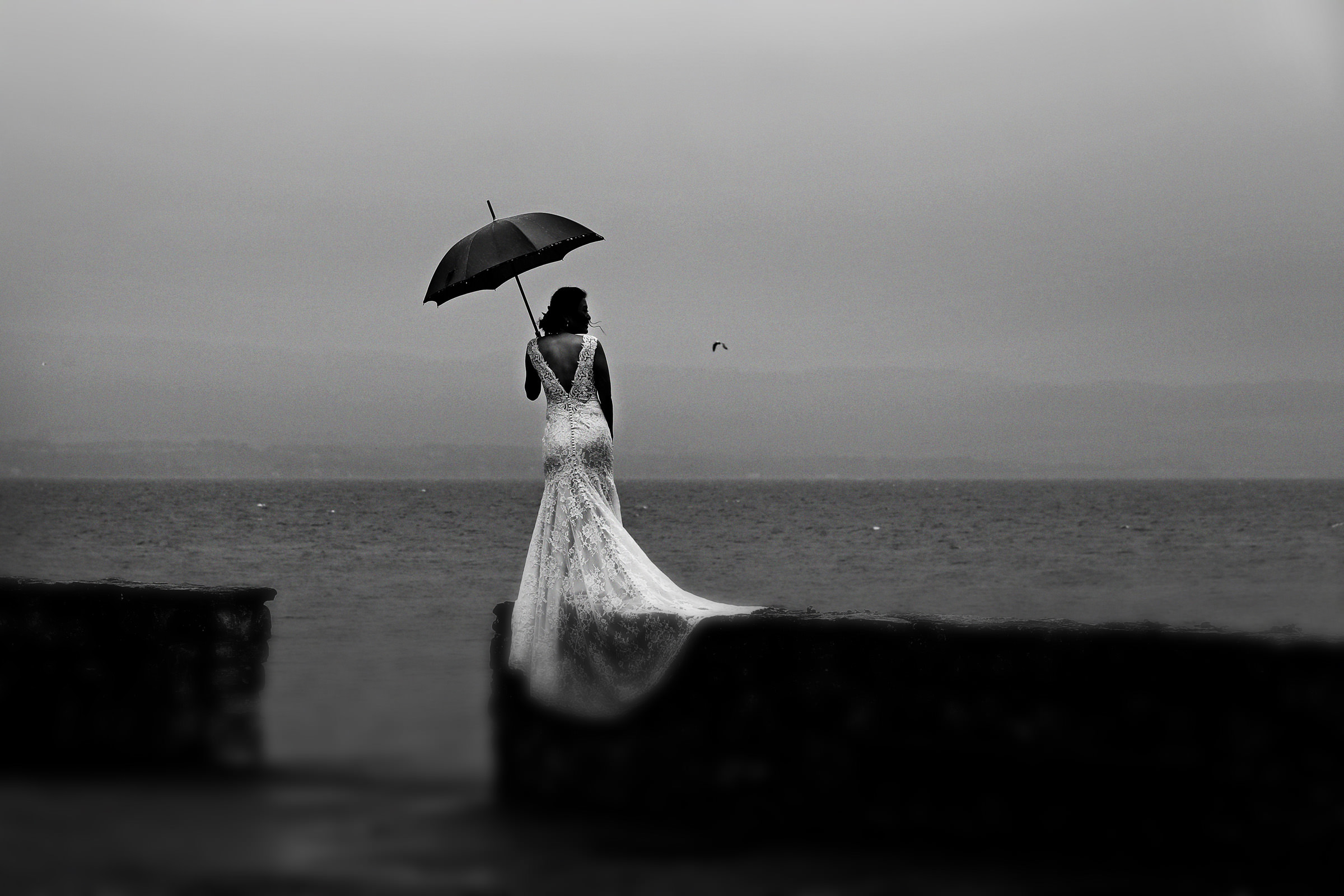 Moody black and white portrait of bride on rainy day by the beach, by Franck Boutonnet