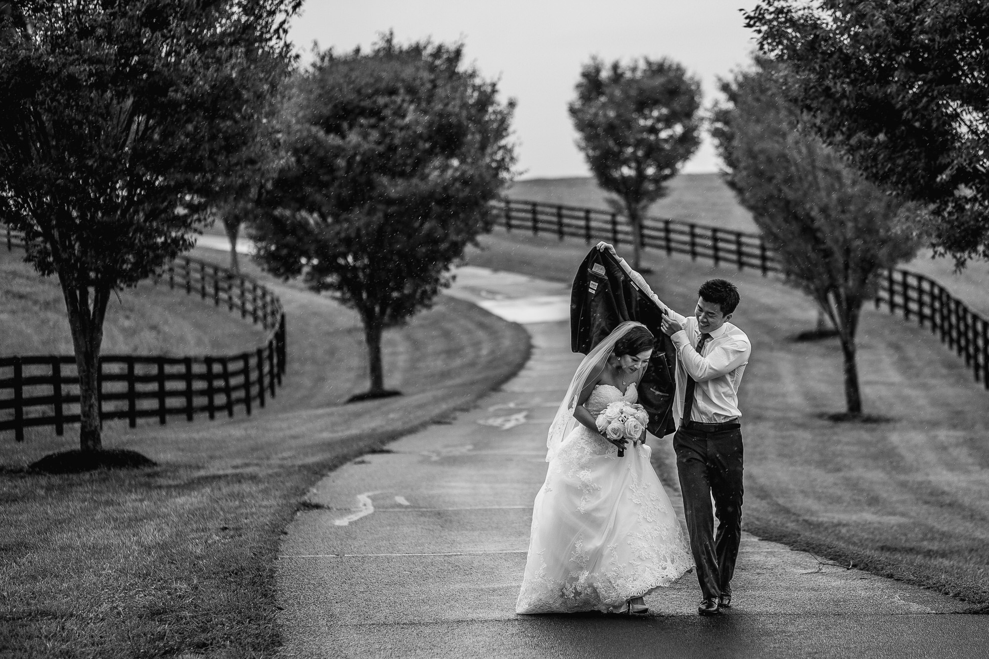 Groom shelters bride with his jacket  - photo by Ken Pak