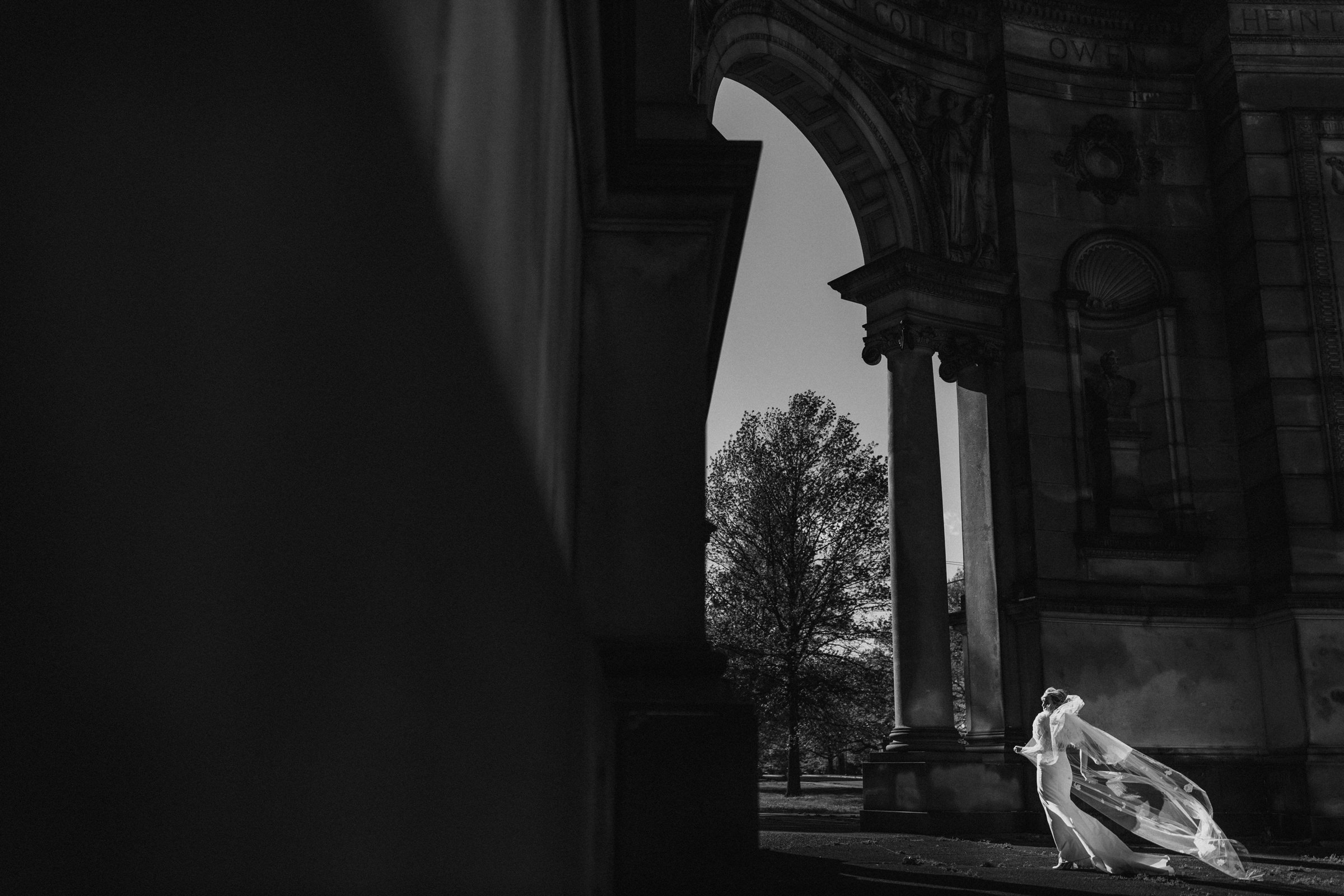 Bride with dramatic veil against archway - Photo by Susan Stripling Photography