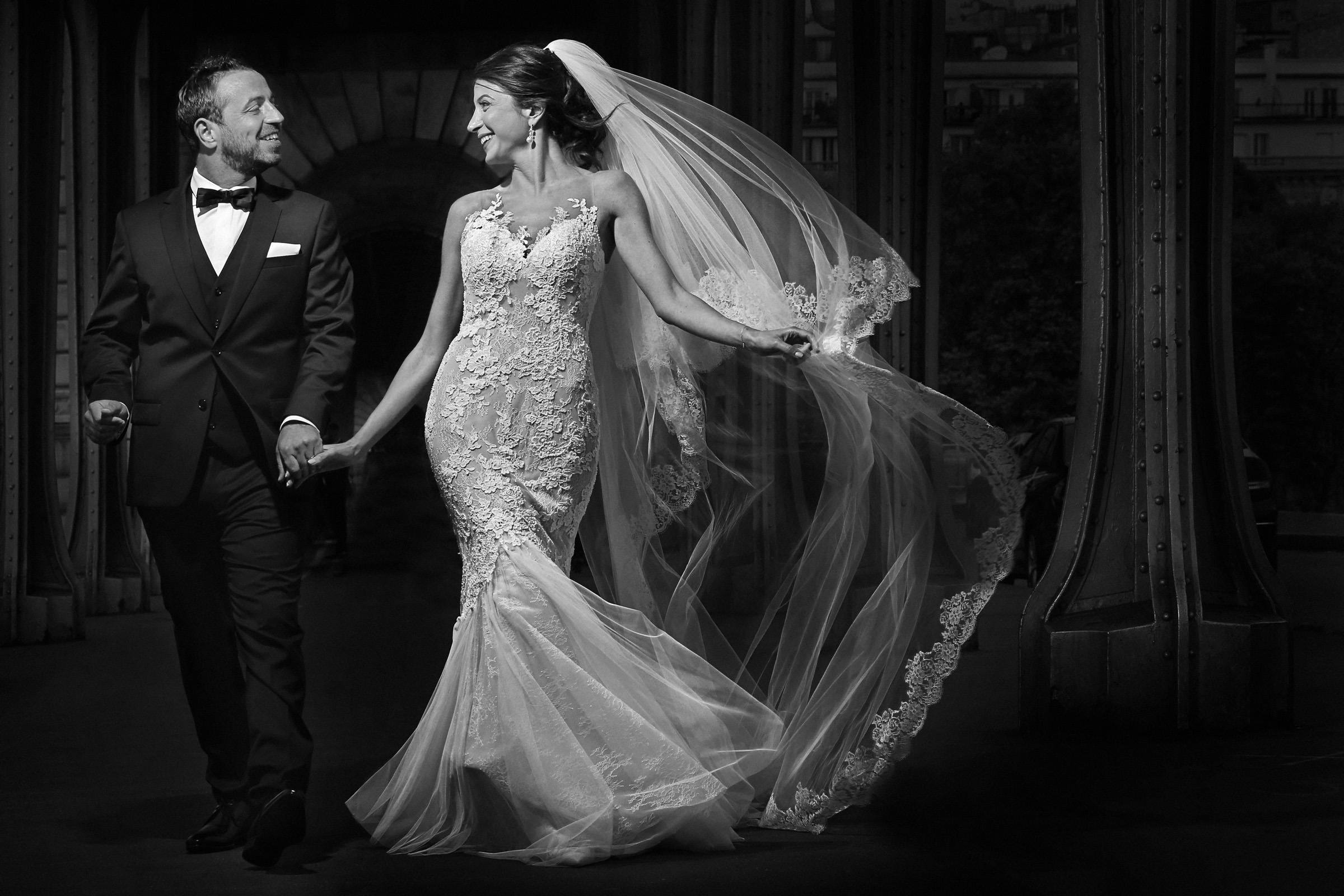 Bride and groom joyfully walking towards camera, by Franck Boutonnet
