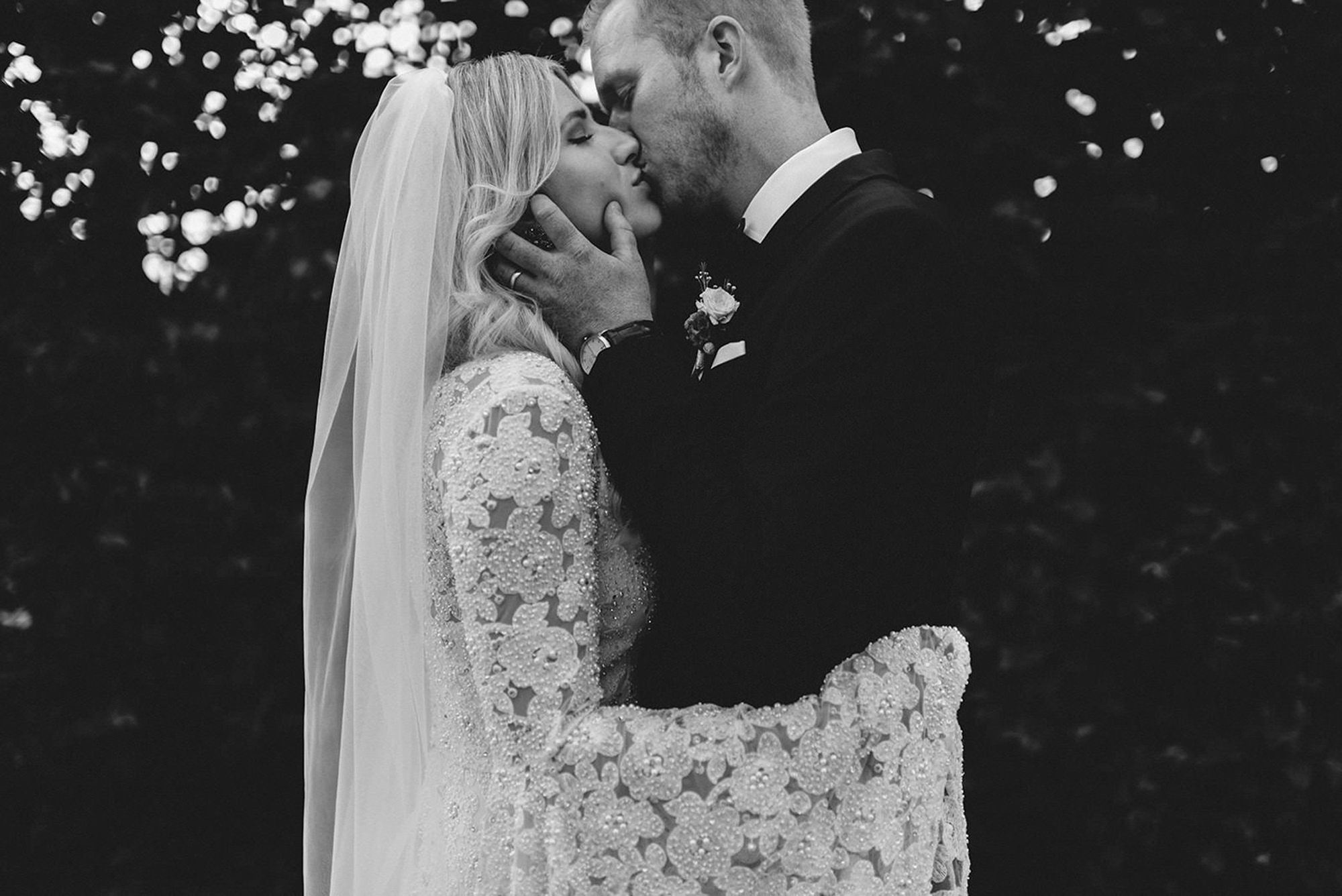 Black and white of bride and groom kissing, by Thierry Joubert