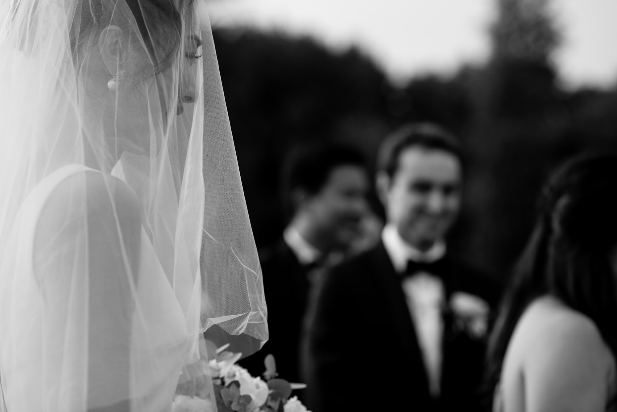 Closeup black and white of bride approaching groom by Thierry Joubert