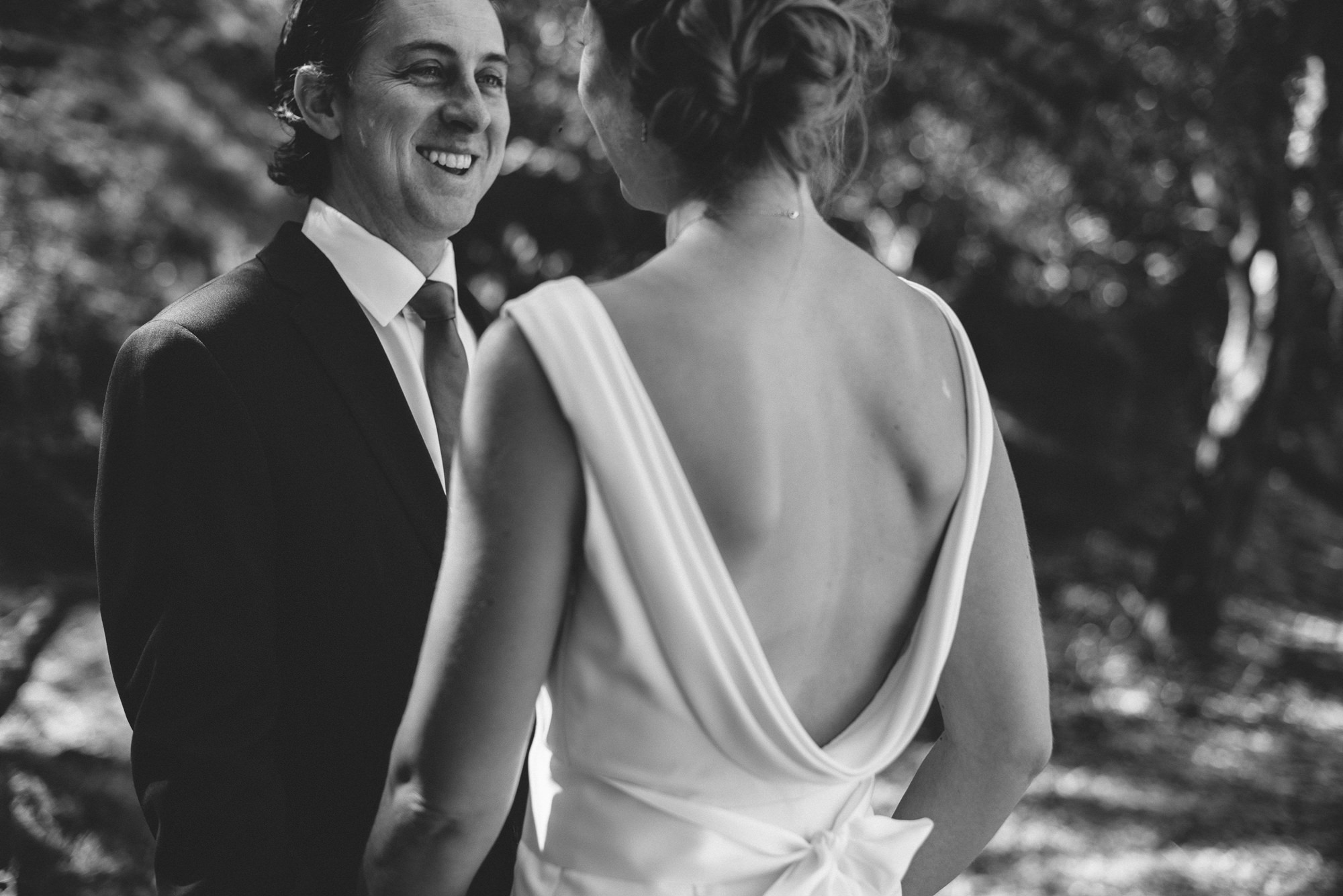 Black and white of bride in backless gown with groom, by Thierry Joubert