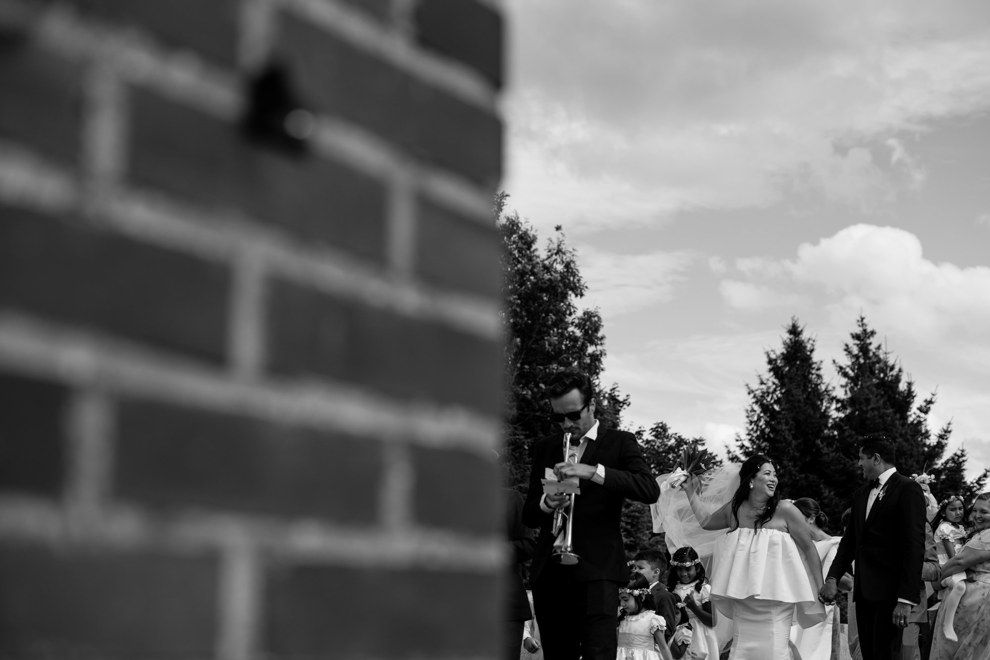 Bride and groom walking with wedding party, by Thierry Joubert