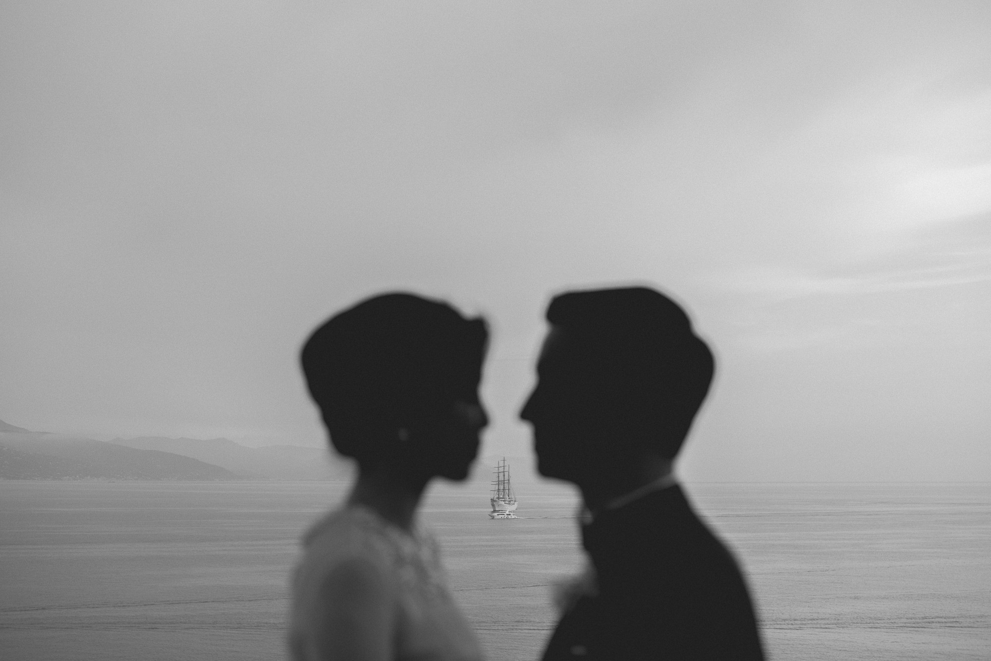 Black and white photo of couple's silhouette with ship in background, by Thierry Joubert