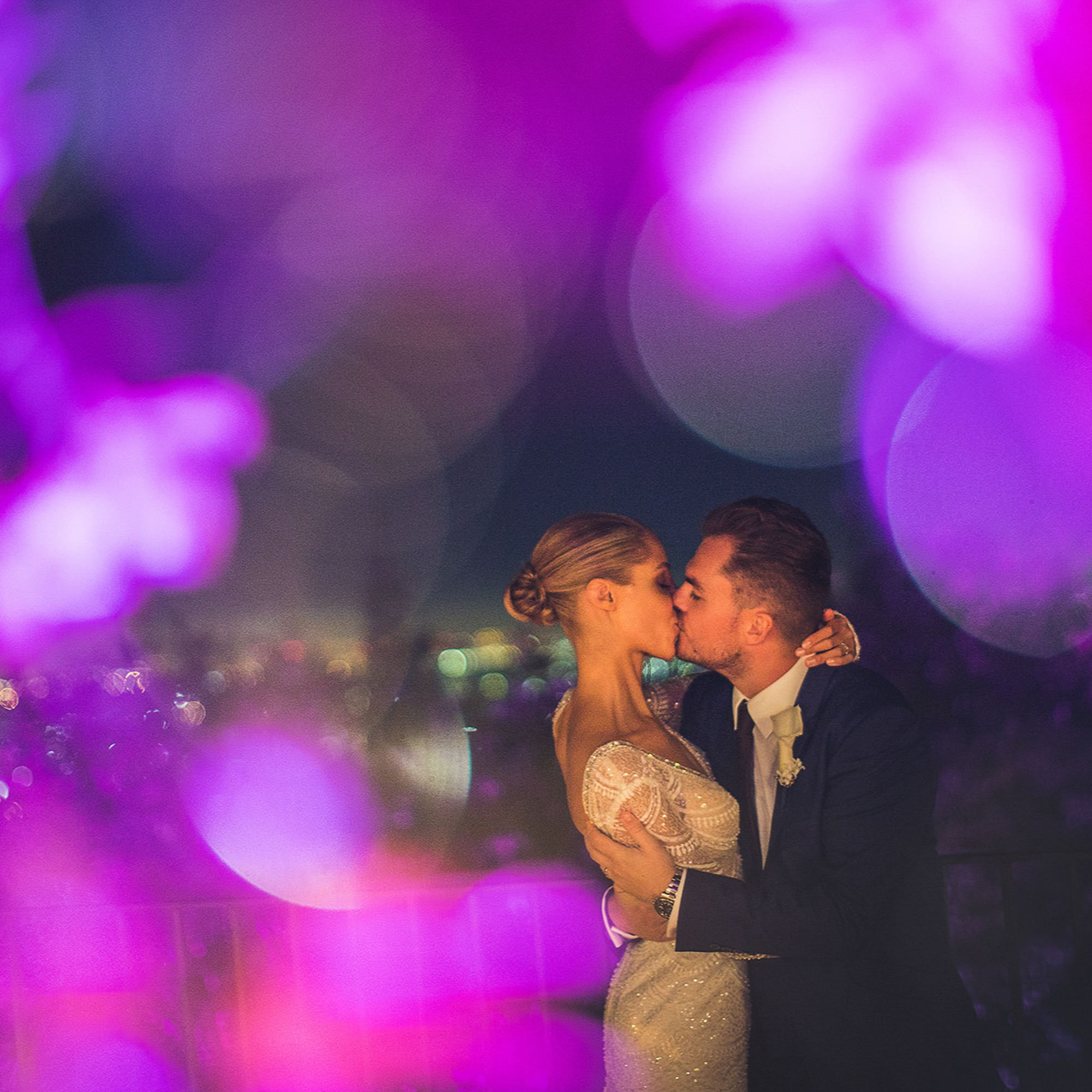 Bride and groom kiss framed by bokeh of purple lights, by Jeff Newsom