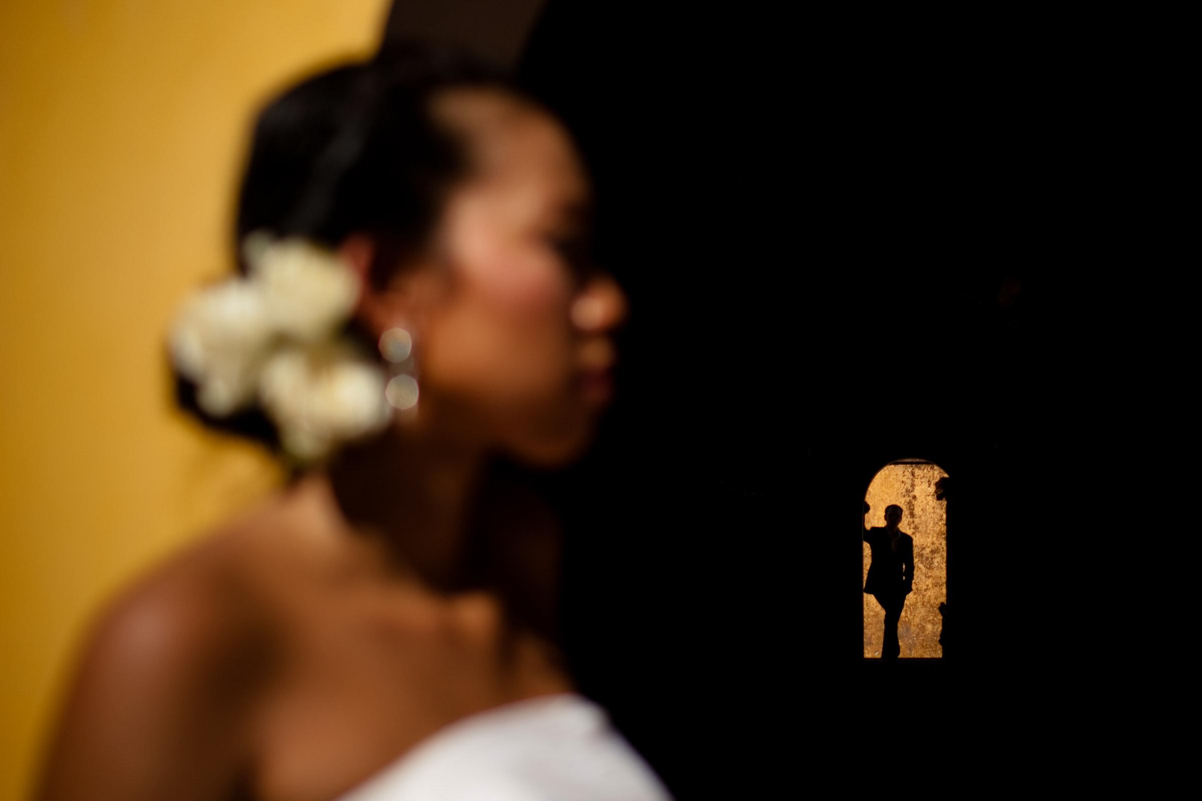 Bride against silhouette groom in doorway - Photo by Wainwright Weddings