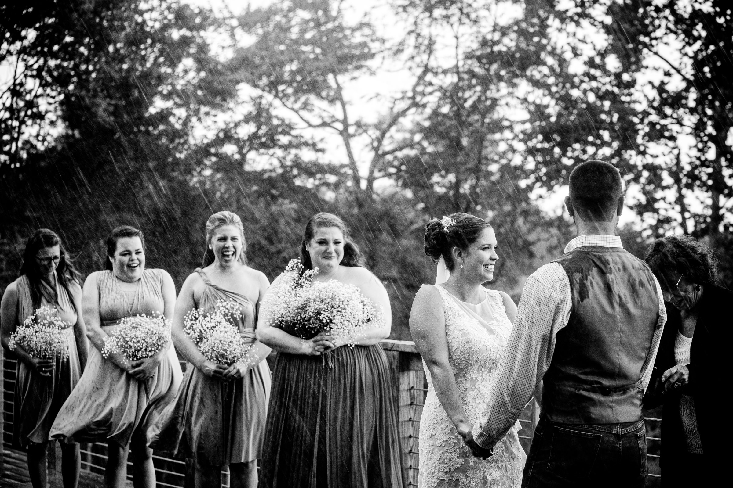 Bride and bridesmaids react to ceremony in the pouring rain - photo by Bee Two Sweet