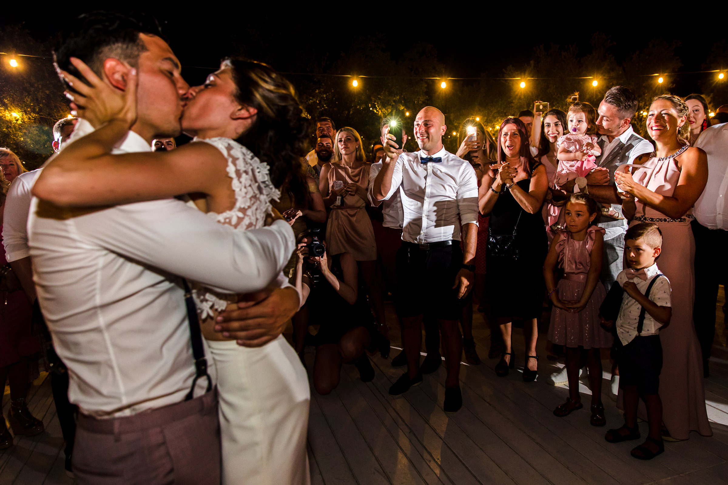 Bride and groom kiss on dancefloor as guests take photos and clap, photo by Philippe Swiggers