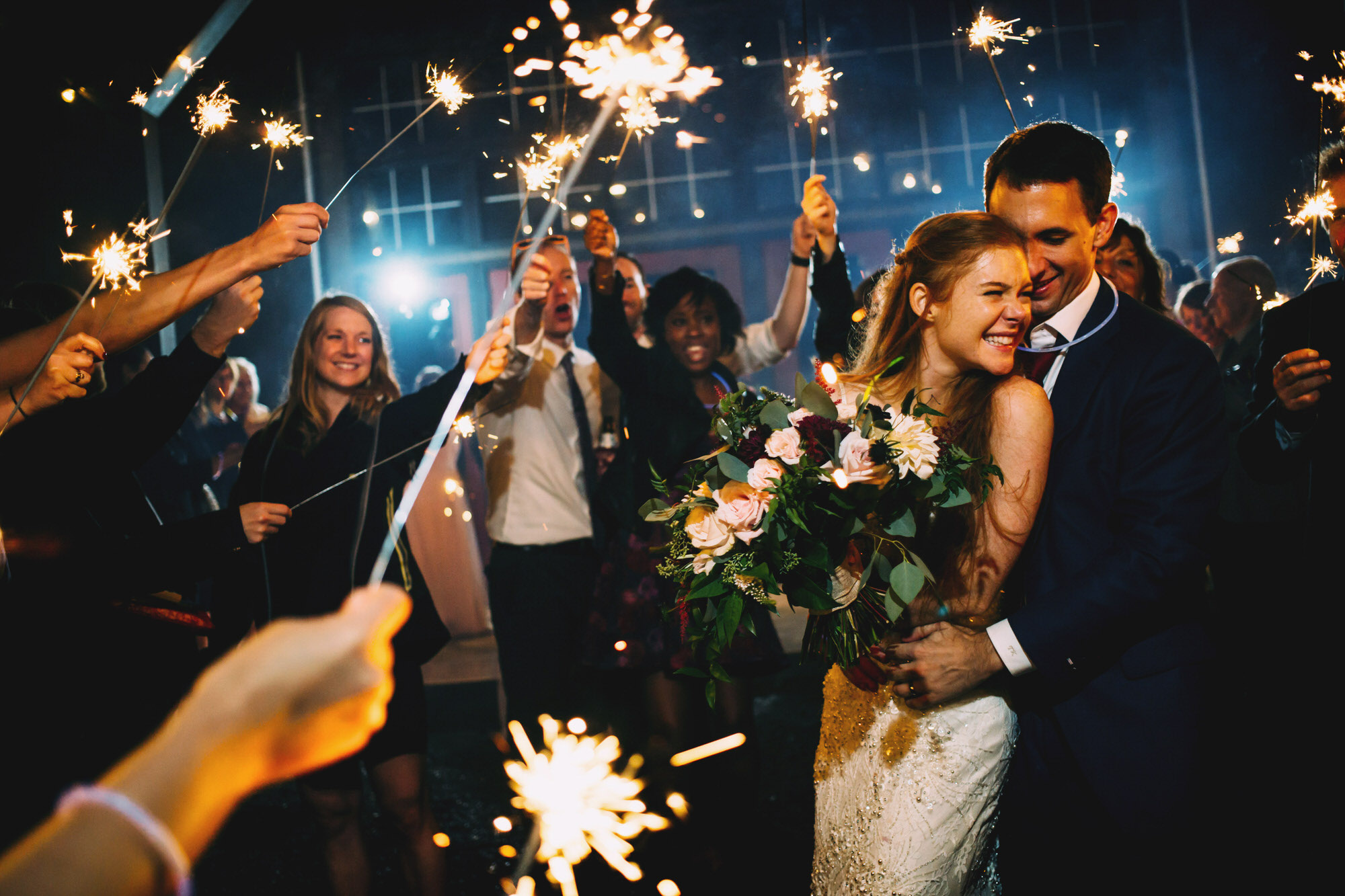Bride and groom embrace amidst sparklers - photo by Ken Pak
