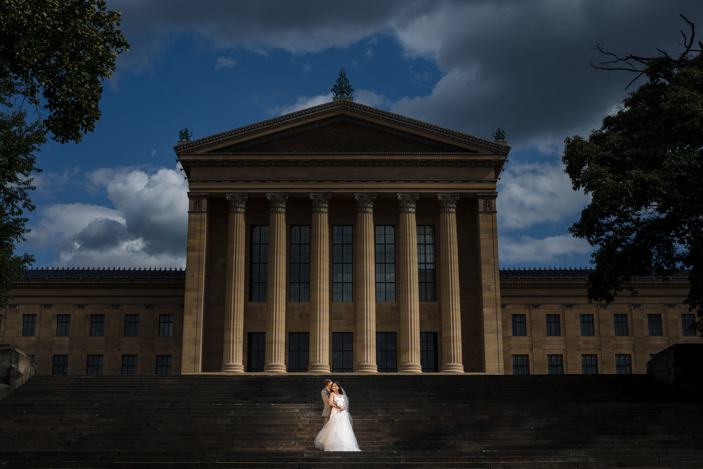 Bride and groom in front of classical architecture - Photo by Susan Stripling Photography