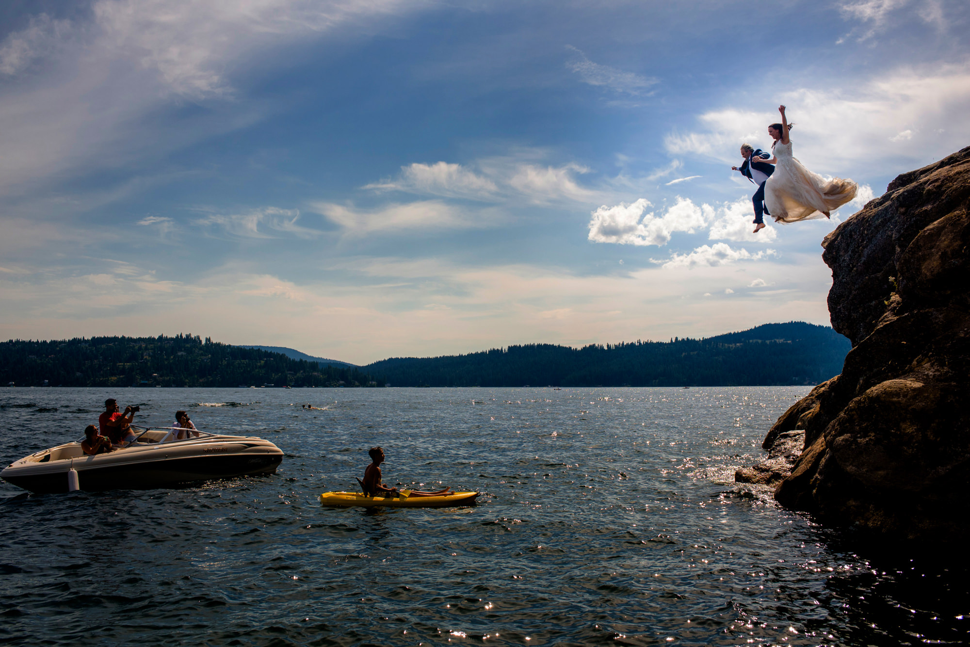 Bride and groom jump into ocean from cliff, photo by The Chrismans