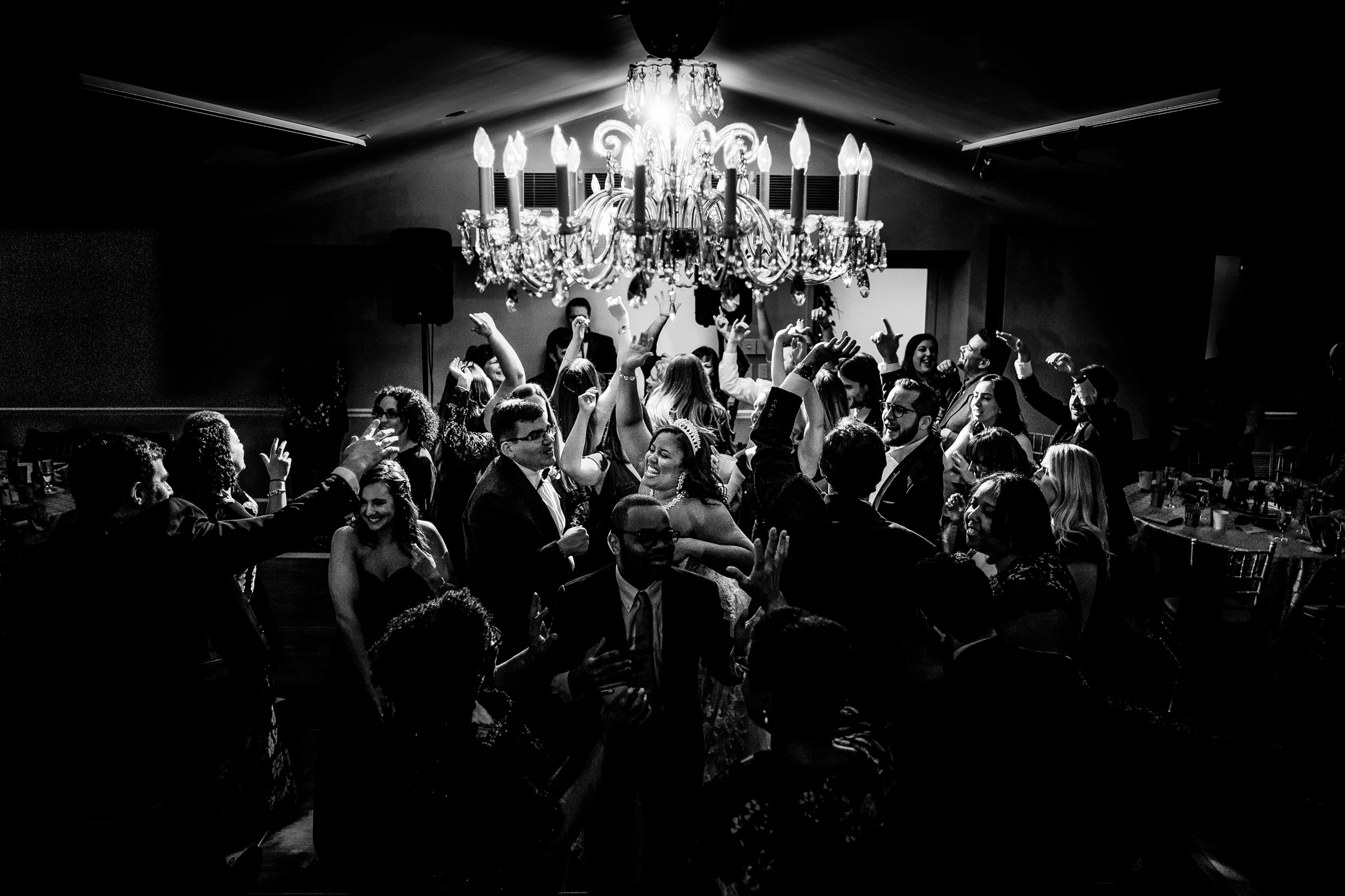 Bride and groom party with guest under chandelier - photo by Bee Two Sweet
