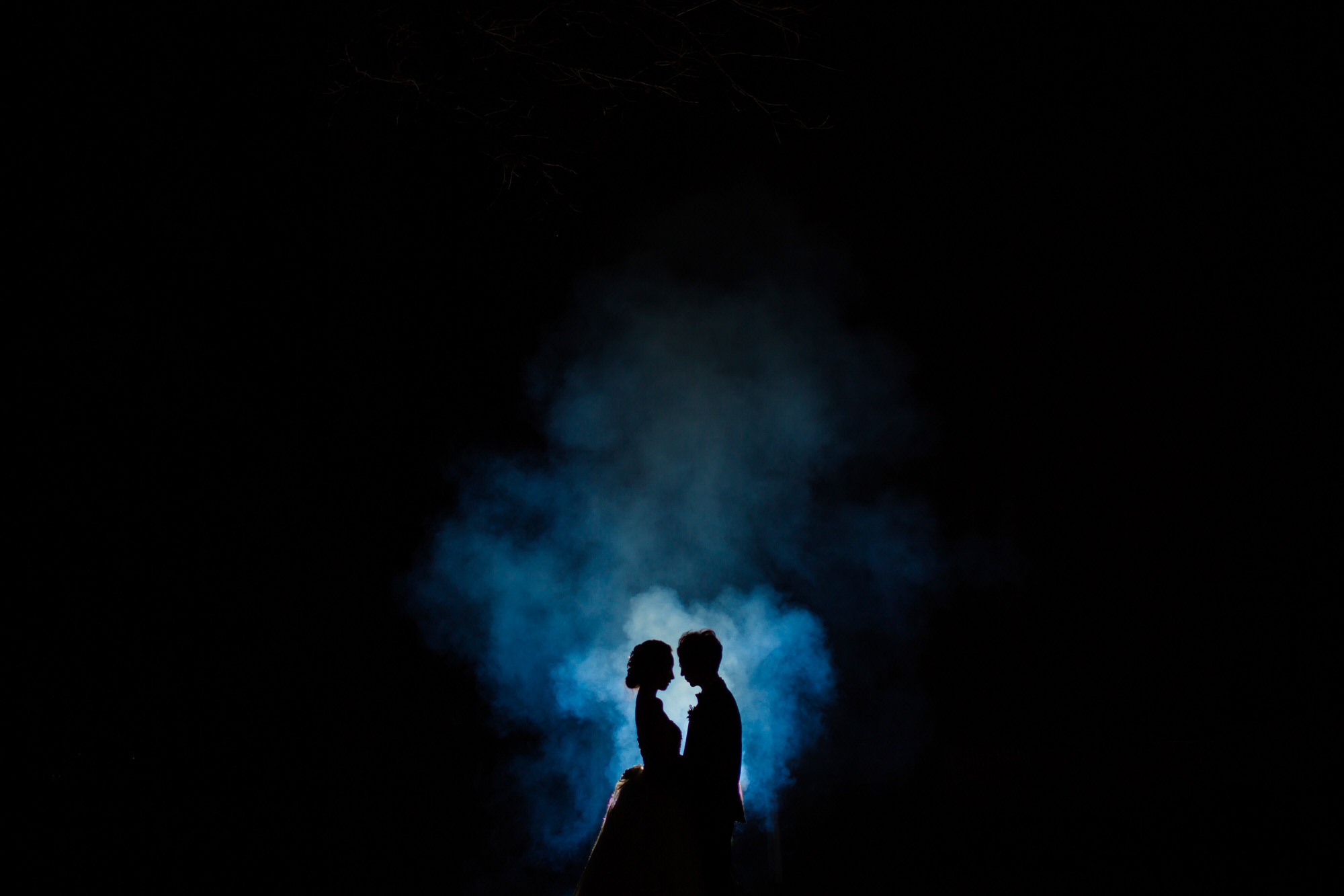 Couple face to face silhouette against blue smoke - photo by Ken Pak
