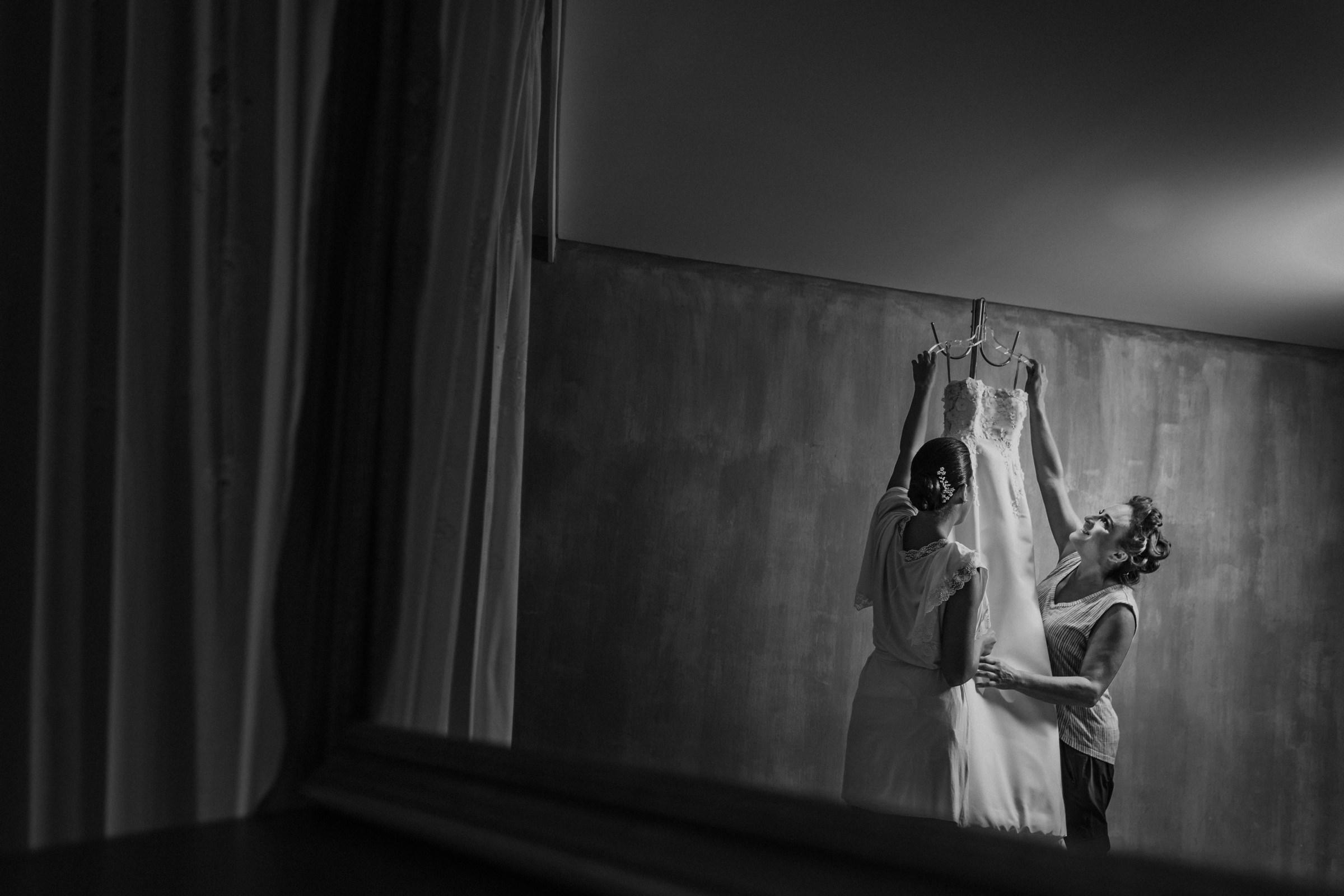 Bride and mom reach for wedding dress .- photo by El Marco Rojo