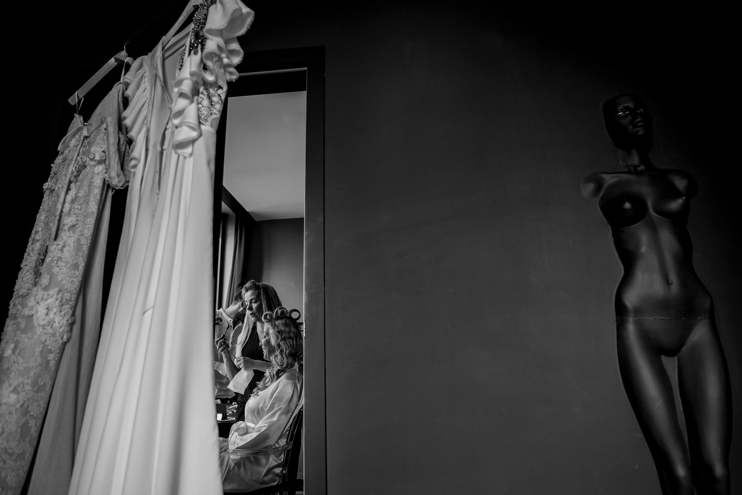 Bride getting ready with wedding dresses in foreground - photo by El Marco Rojo