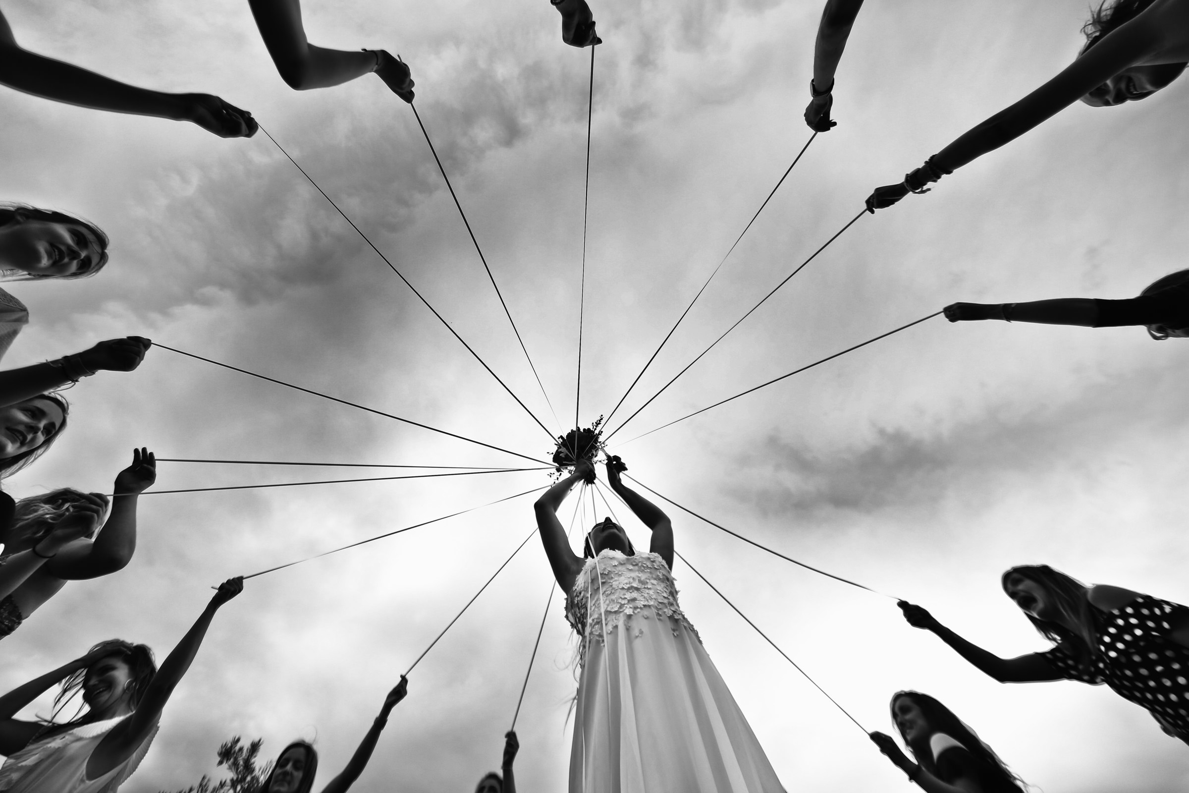 Bride holds up bouquet with ribbons held by wedding party, by Franck Boutonnet