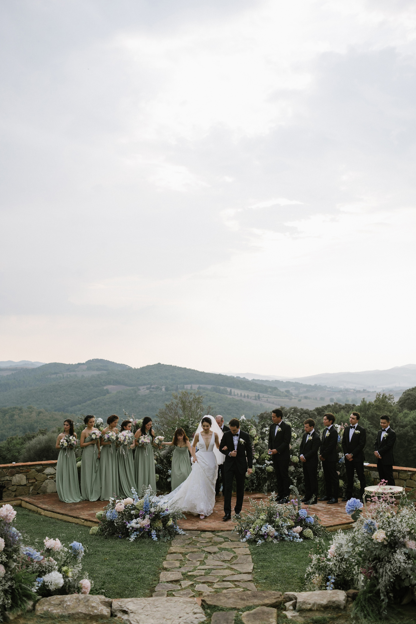 Beautiful overview shot of bride and groom exiting ceremony with French countryside by Thierry Joubert