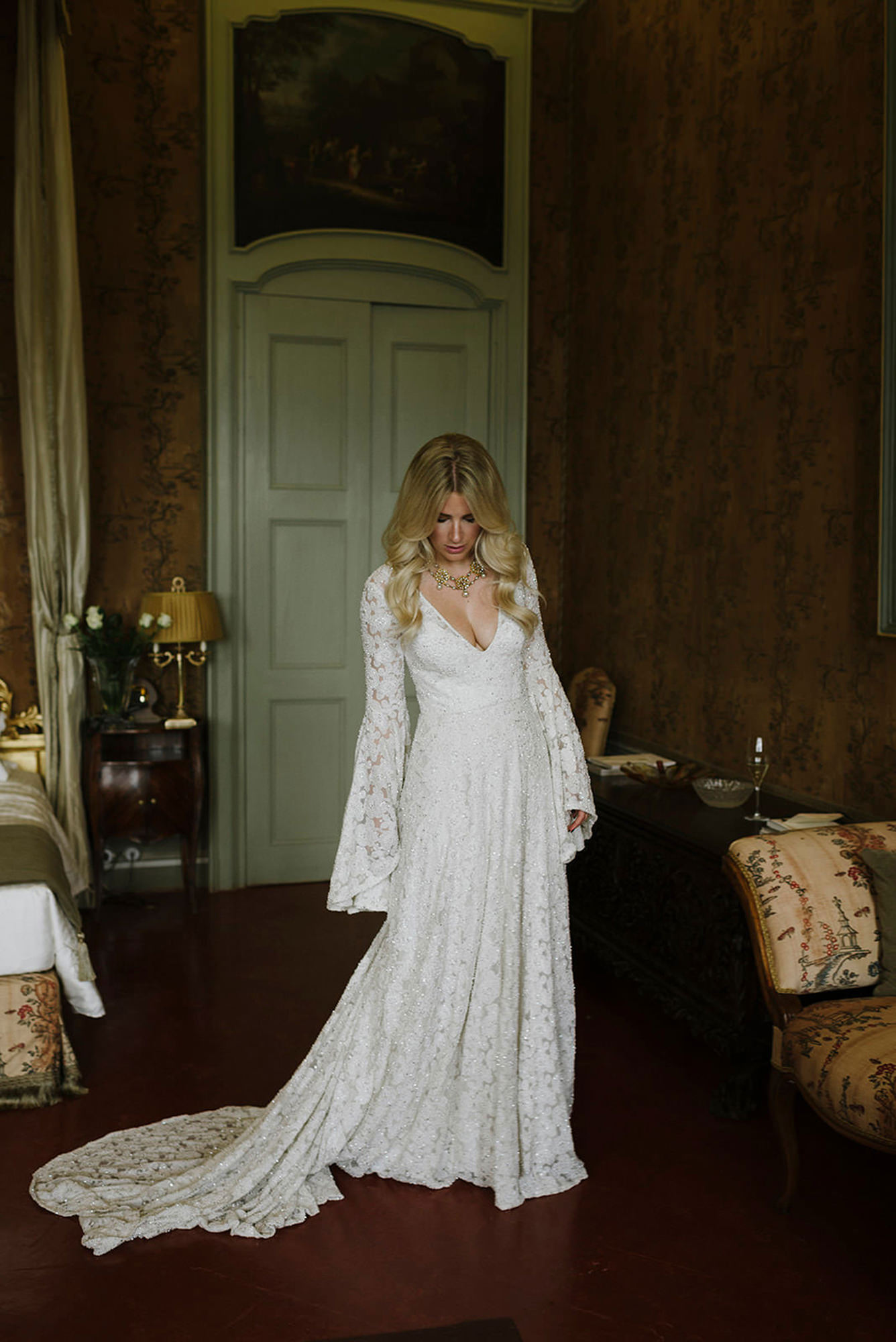 Portrait of bride in beautiful bell-sleeved lace gown, by Thierry Joubert