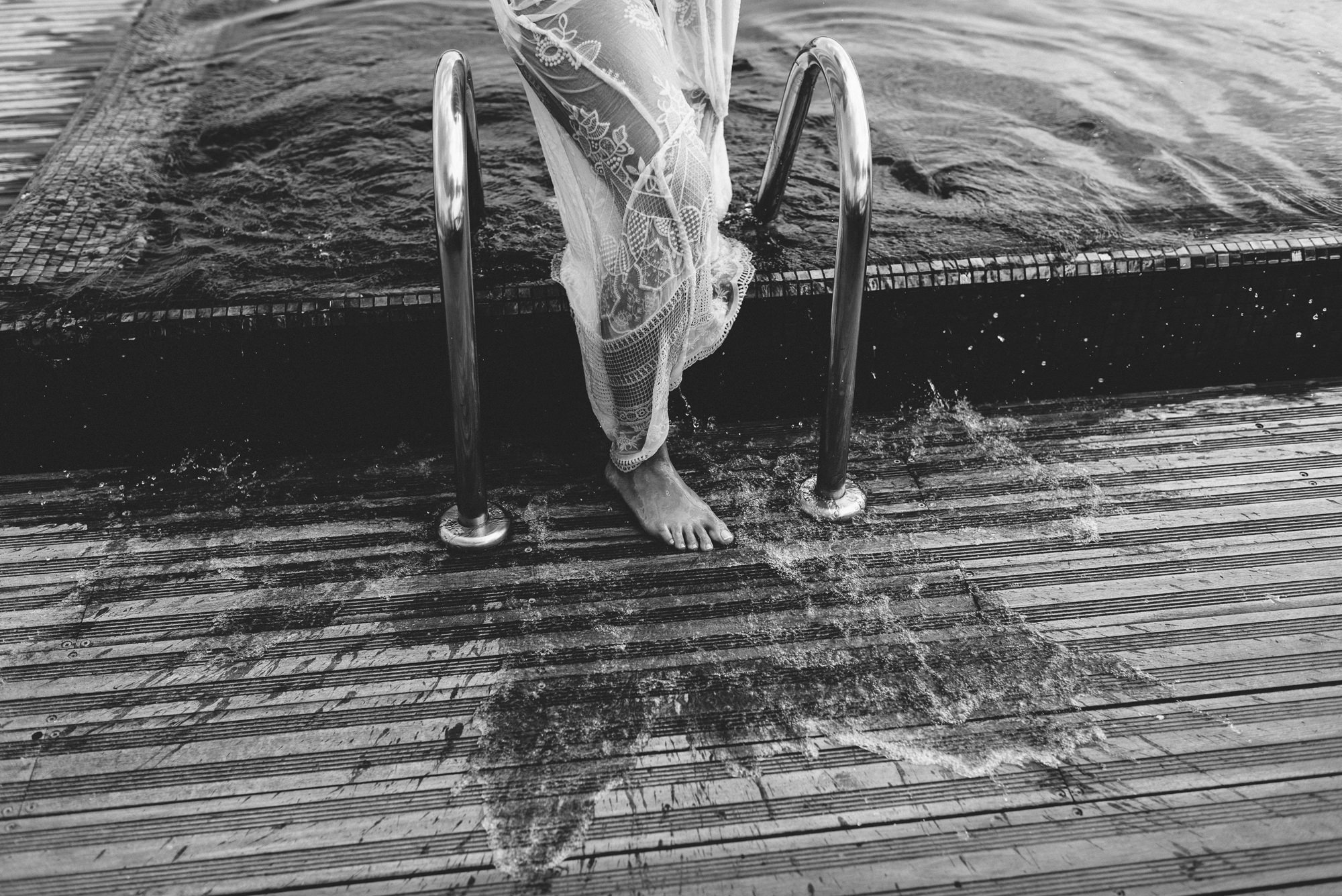 Black and white of bride in wet wedding gown stepping out of pool, by Thierry Joubert