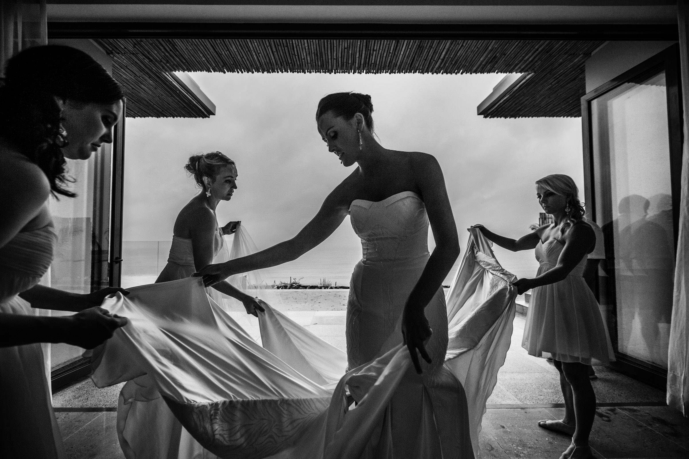 Bridesmaids arranging bride's train - photo by Wainwright Weddings