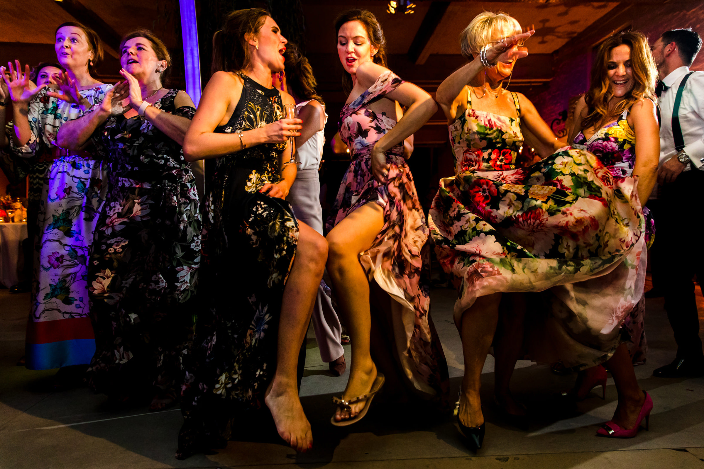 Bridesmaids in colorful flowy dresses dancing, photo by Philippe Swiggers