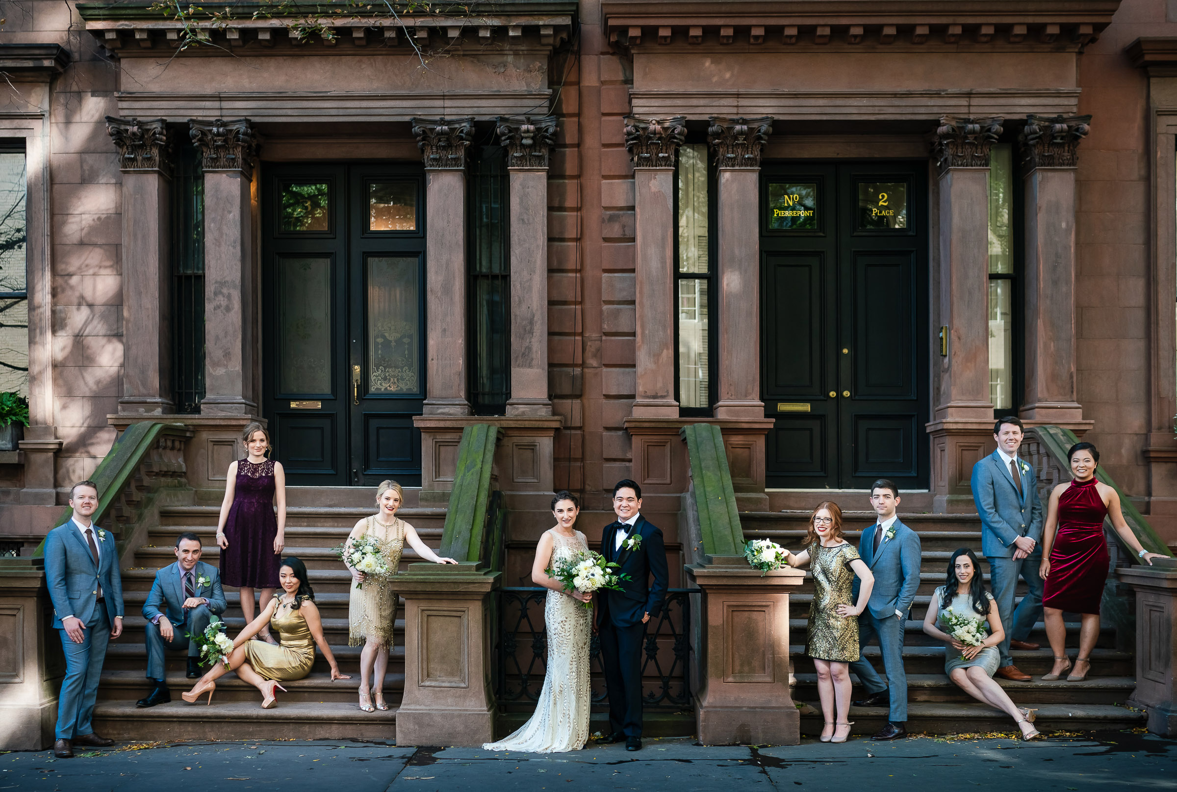 Classic wedding group shot on brownstone stairs - photo by The Brenizers