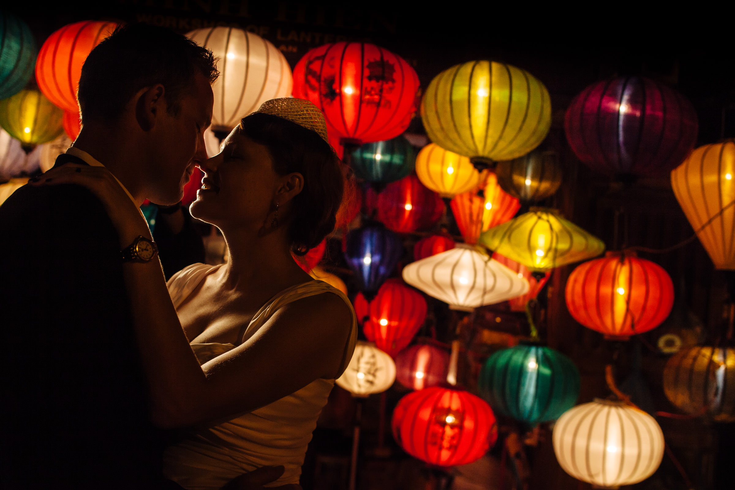 Couple against colorful lanterns - Photo by Wainwright Weddings